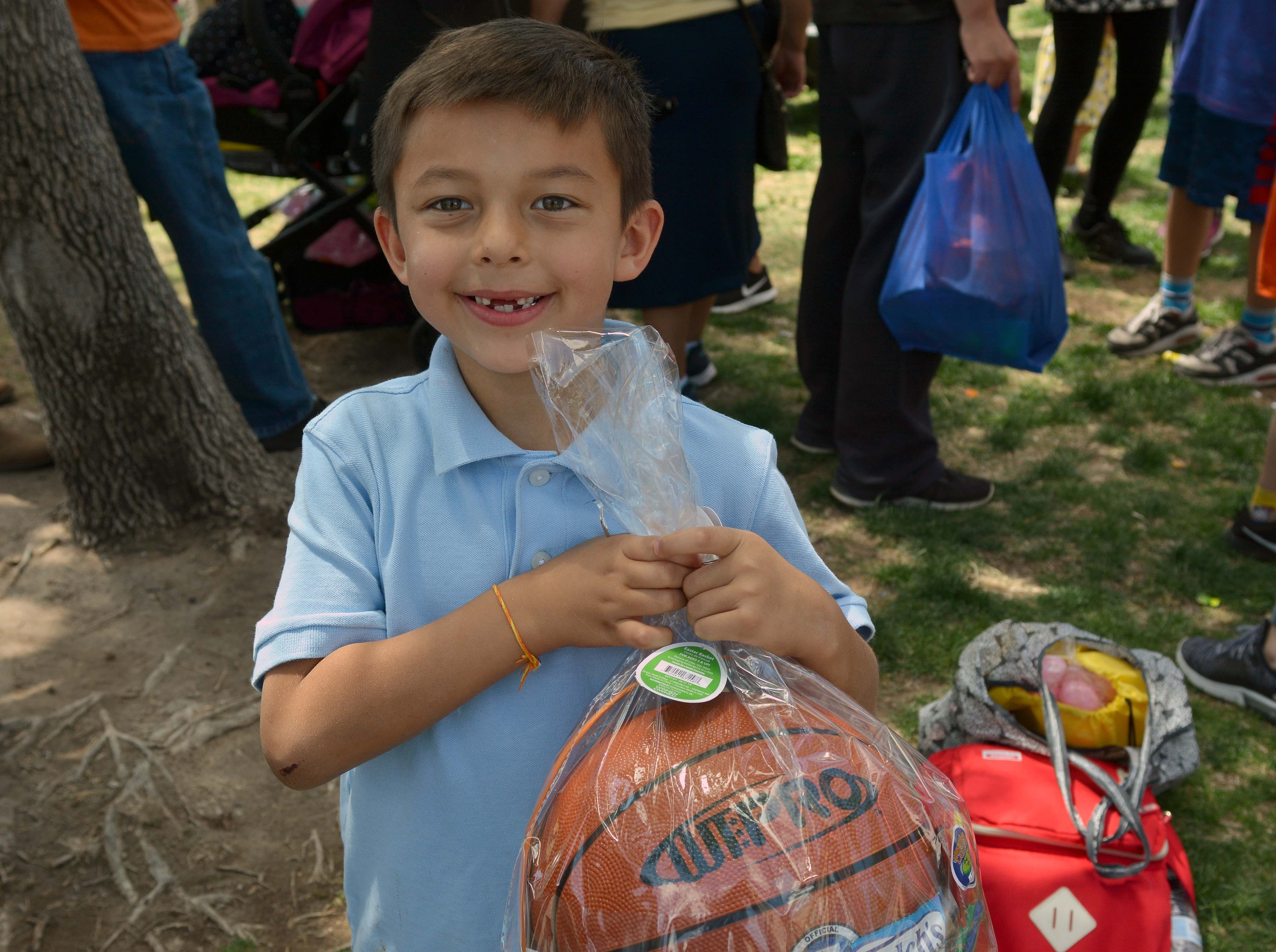 Xzavier Soliz shows off a basket that he won in a raffle during SpringFest at Young Park on Saturday, April 20, 2019.
