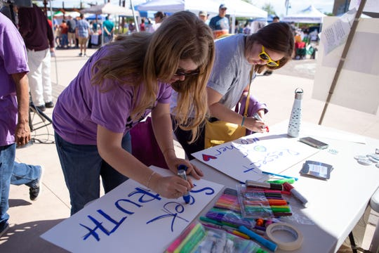 Emily Creegan, left, and Maddie Strong make signs for the March for Science during the Earth Day and March for Science events on the Downtown Plaza on Saturday, April 20, 2019.