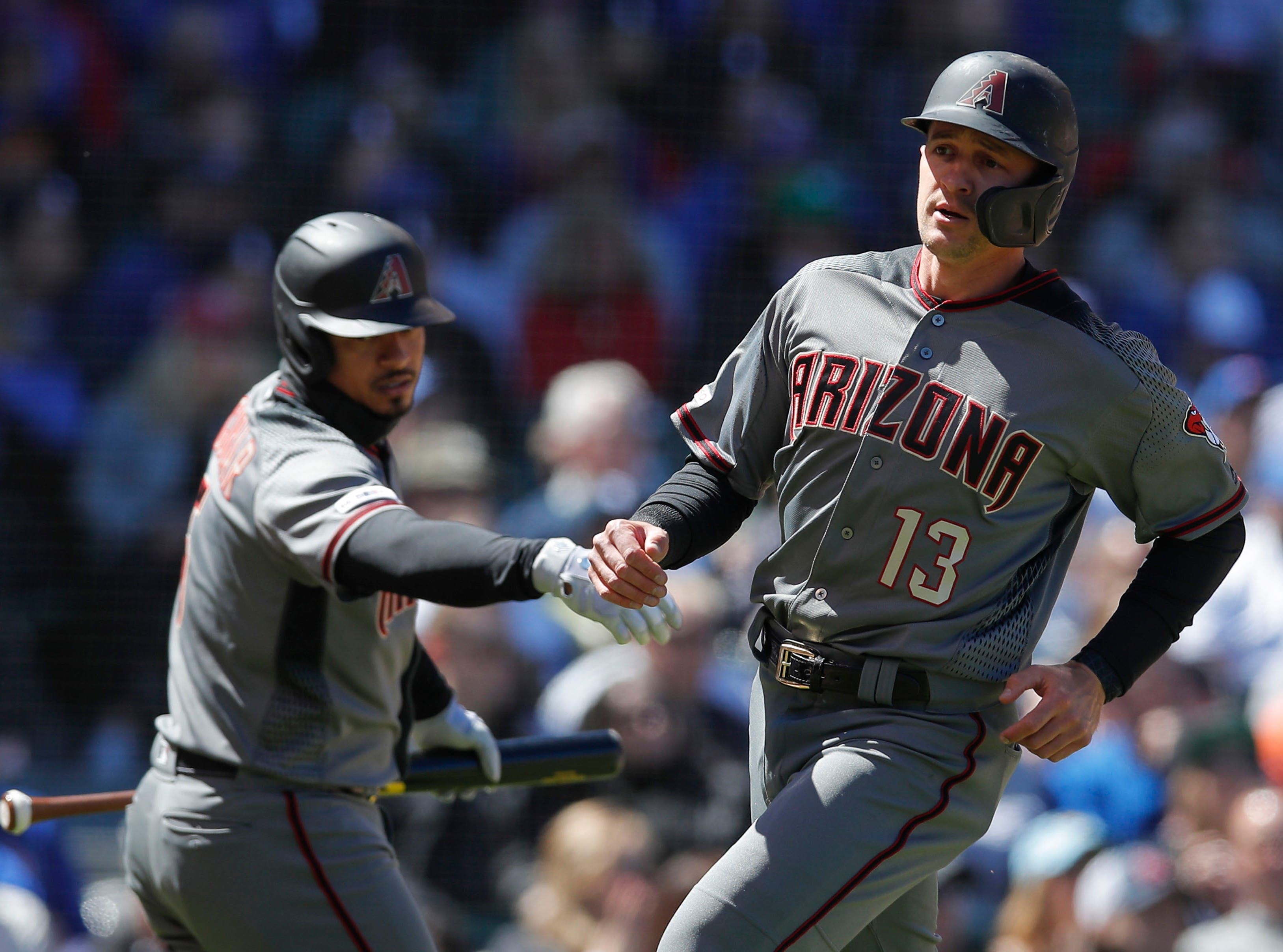 Diamondbacks shortstop Nick Ahmed comes in to scores past third baseman Eduardo Escobar during the second inning of a game April 20 at Wrigley Field.