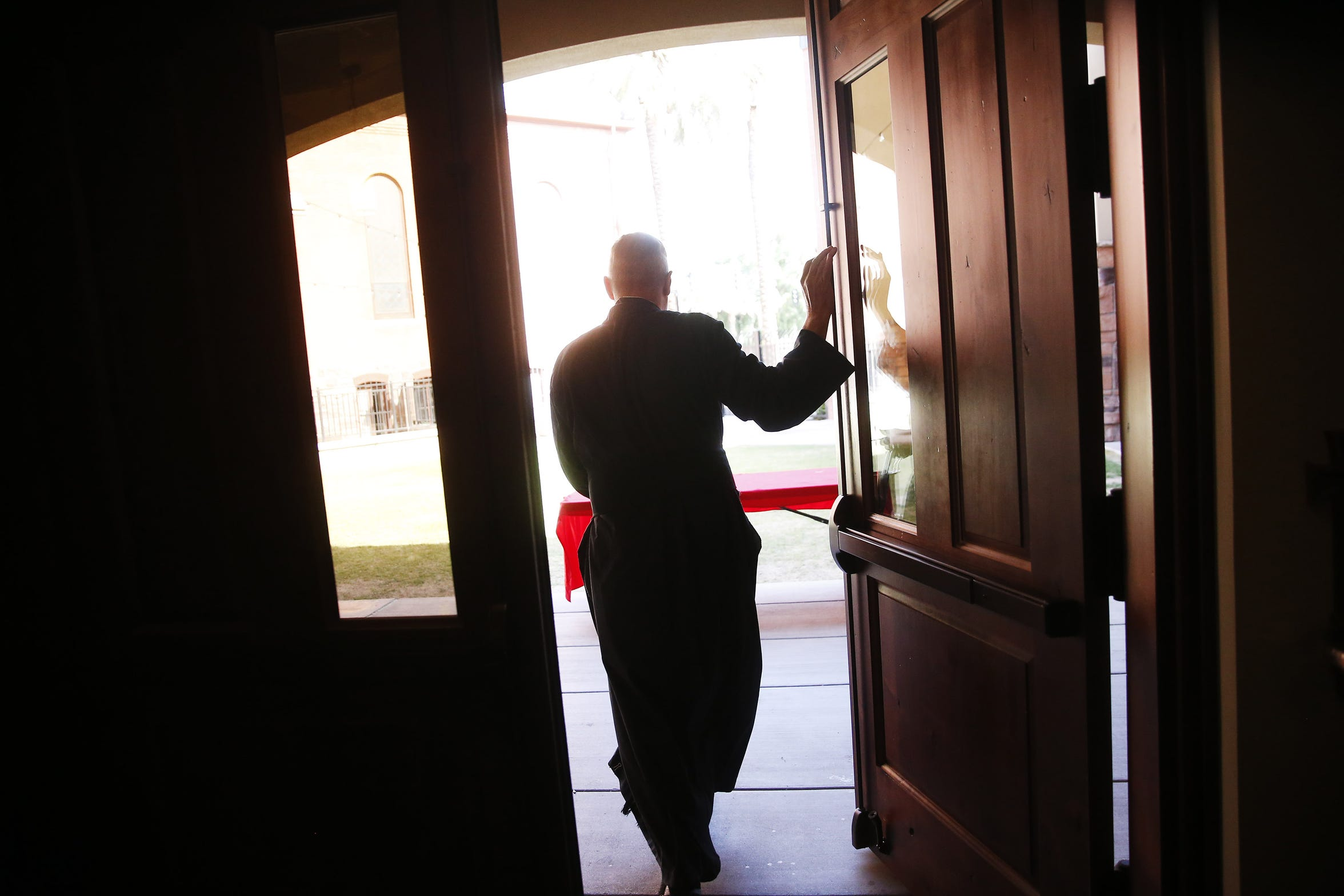 The Rev. Rob Clements walks out to the courtyard of the ASU Catholic Newman Center in Tempe, Ariz. April 14, 2019.