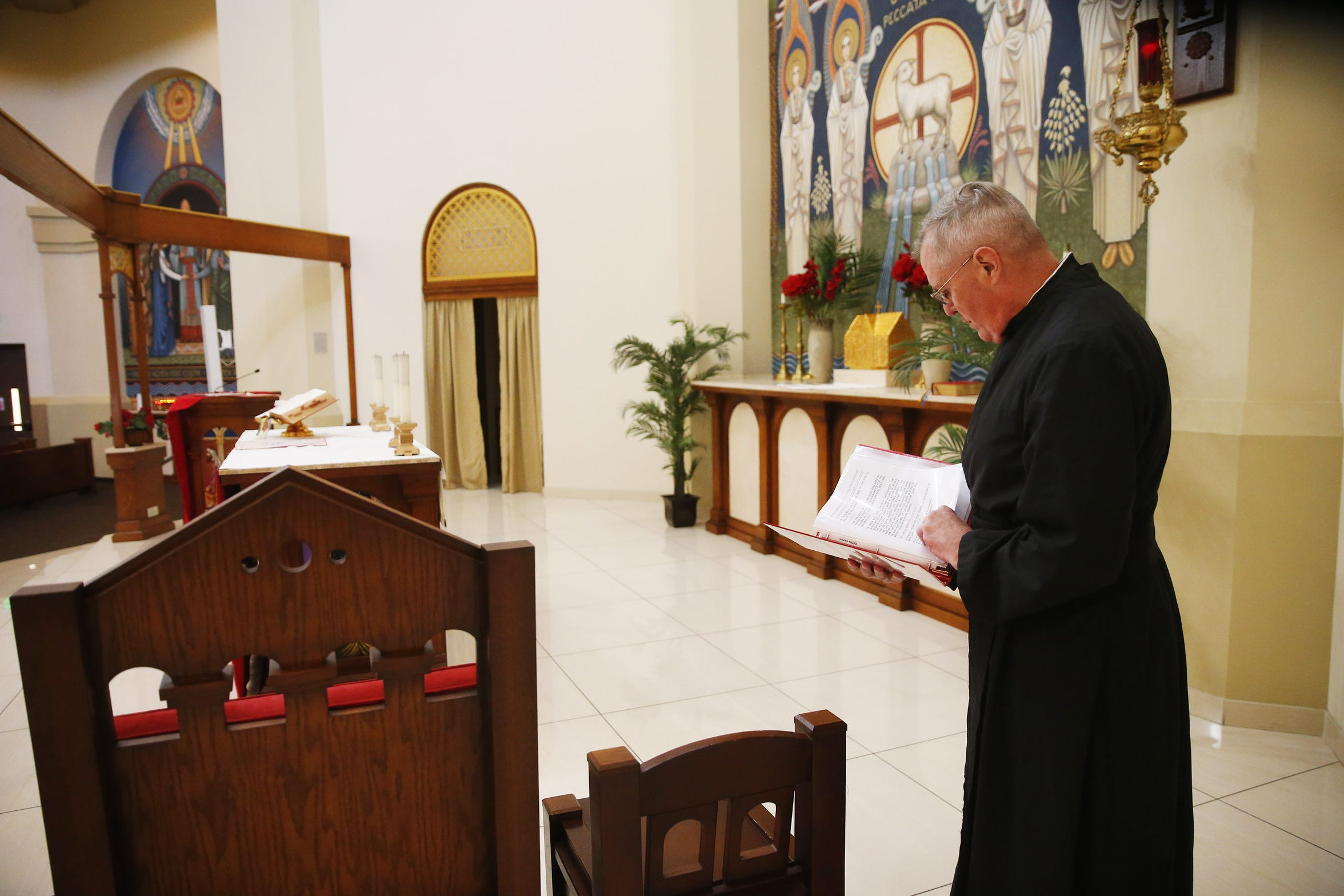The Rev. Rob Clements prepares for Palm Sunday mass at the ASU Catholic Newman Center in Tempe, Ariz. April 14, 2019.