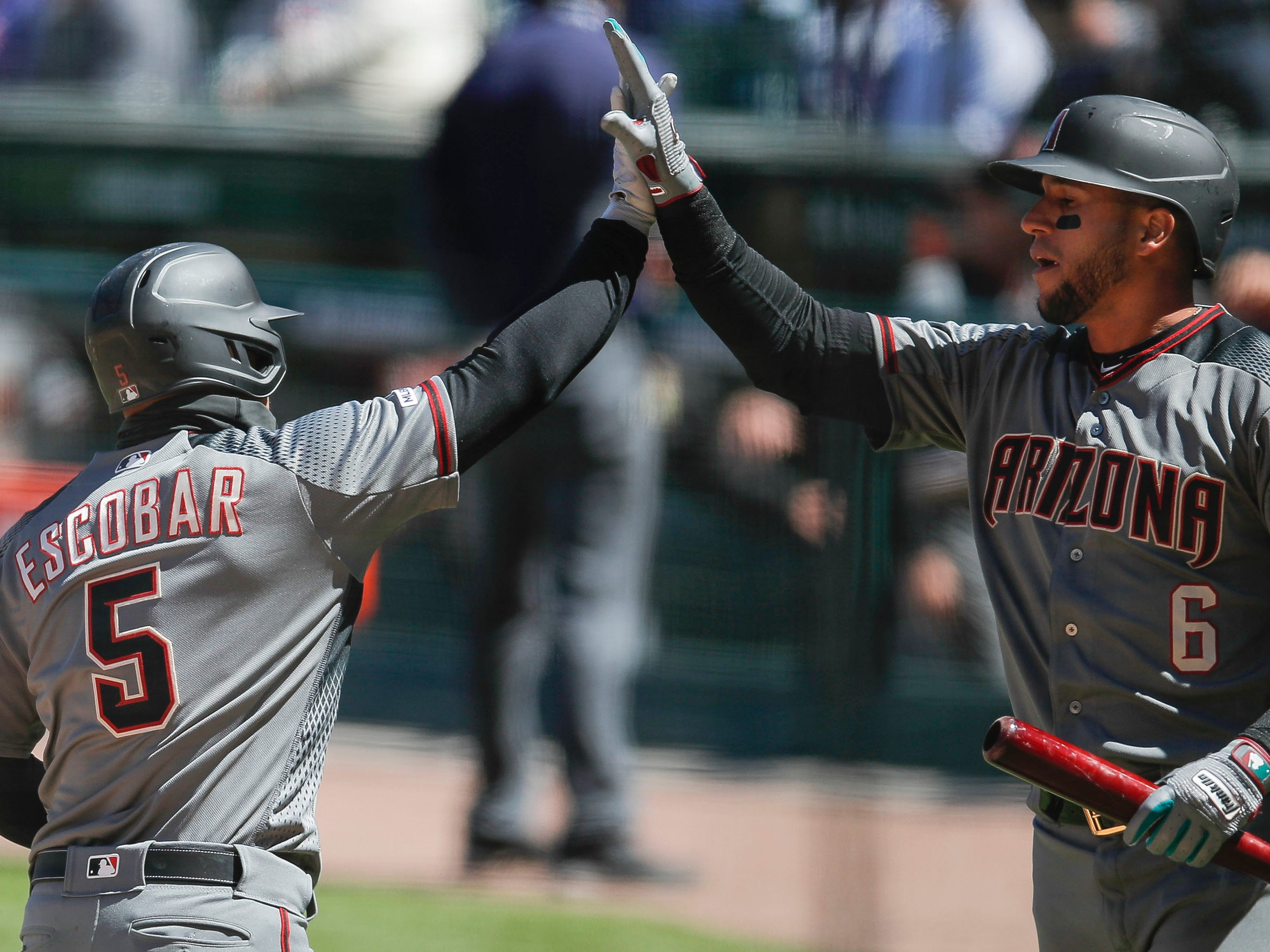 Diamondbacks third baseman Eduardo Escobar (5) celebrates his home run against the Cubs with right fielder David Peralta (6) during the first inning of a game April 20 at Wrigley Field.