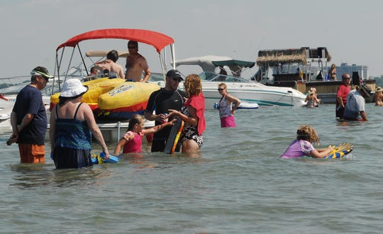 Families play in the water near their boat in Lake Huron a few years ago.