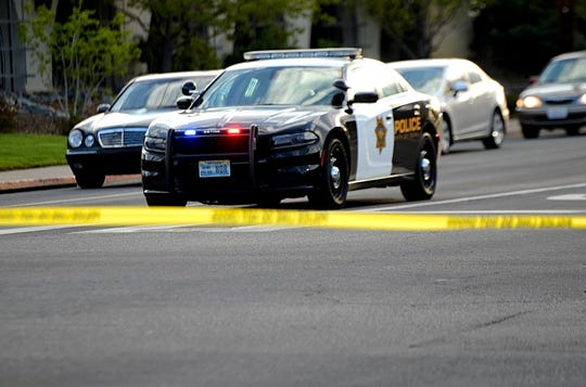 A photo of a Reno police vehicle blocking traffic behind a line of crime tape.