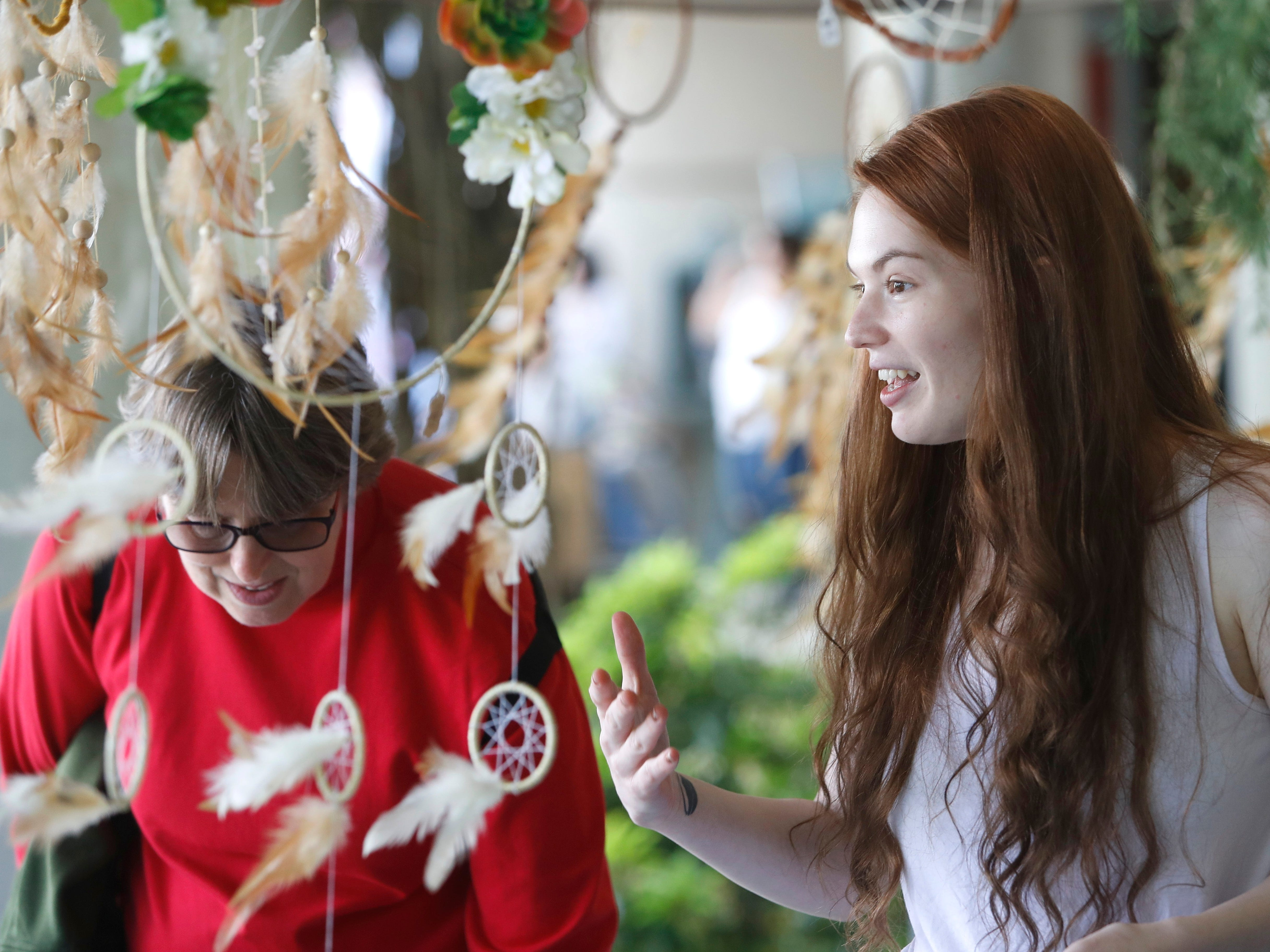 Devan Sheehy of Redding talks to customers Saturday at her dreamcatchers booth during the Whole Earth and Watershed Festival at Redding City Hall.