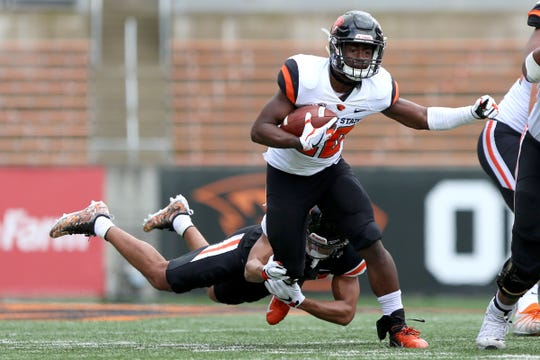 Defensive back Isaiah Dunn (23) attempts to take down Running back B.J. Baylor (20) during Oregon State University's spring football game at Reser Stadium in Corvallis on April 20, 2019.