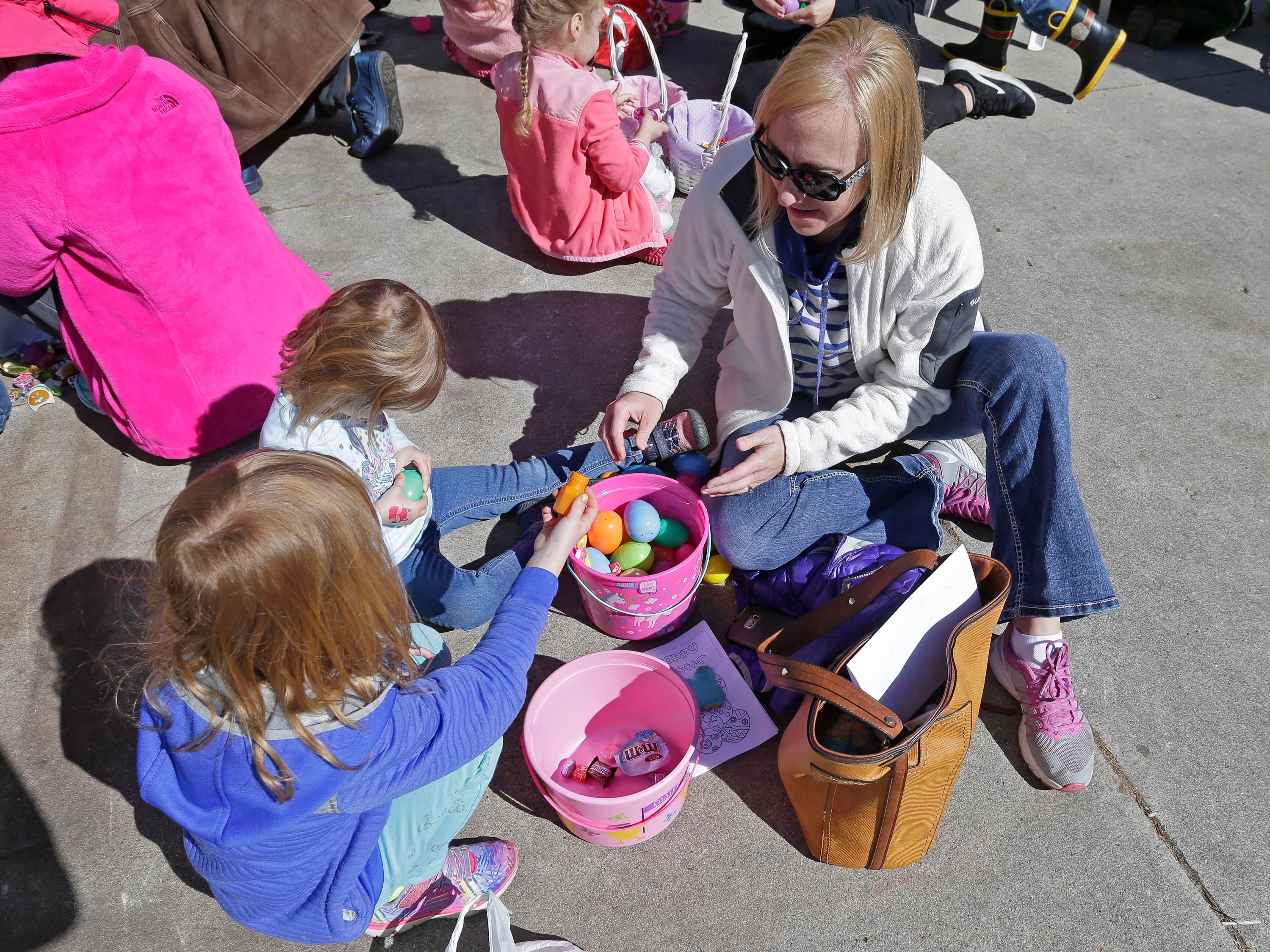 Melissa Munger, of Cleveland, Wis, right, helps her daughters Marcella, 6, and Cecilia, 3, open their easter eggs following the Hocevar Easter Egg Hunt, Saturday, April 20, 2019, in Sheboygan Falls, Wis.  This years marks 25 years for the Hocevar Family holding an Easter egg hunt at their home, according to Kathy Hocevar.