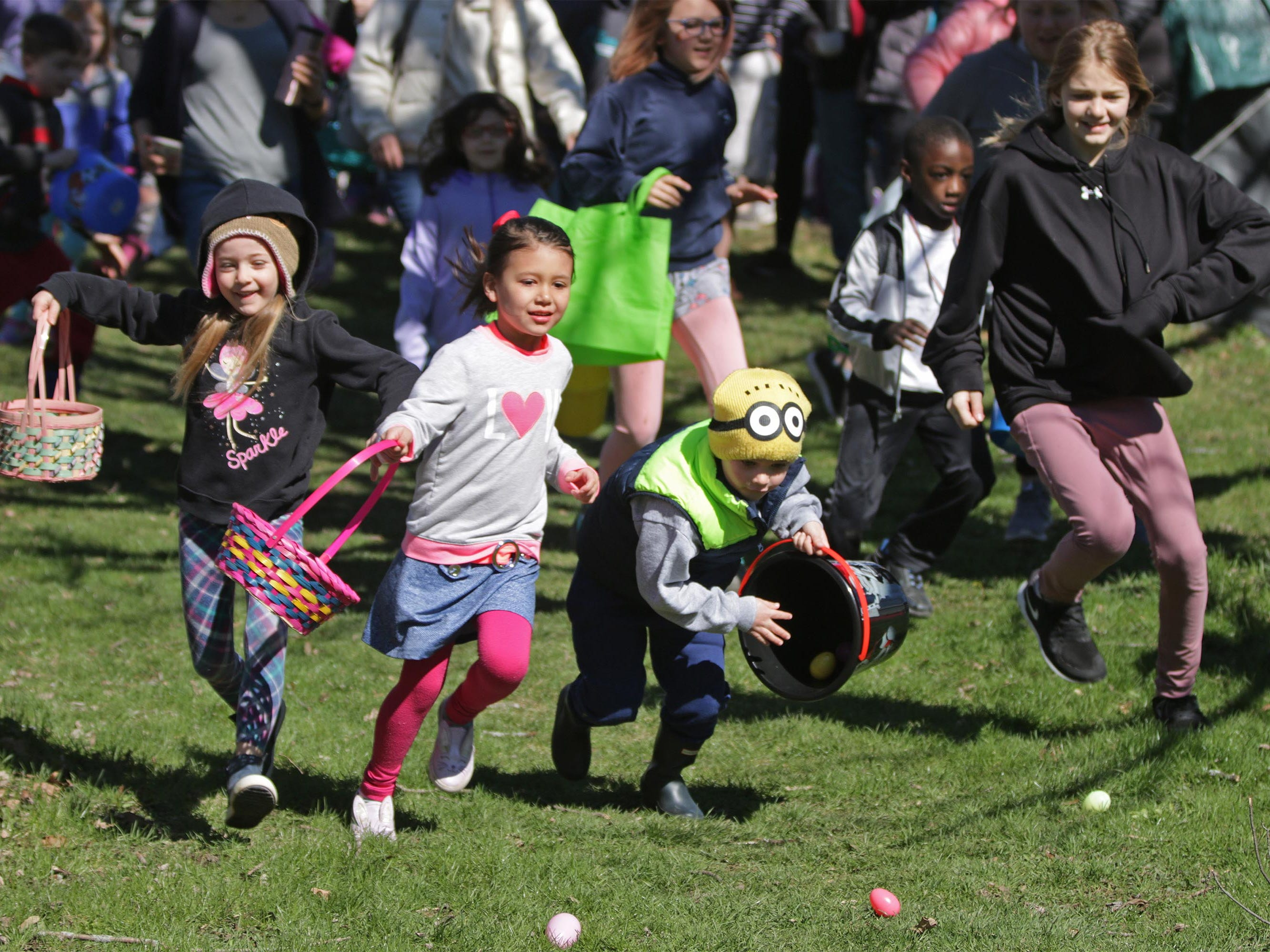Children scamper to gather eggs at the annual Hocevar Easter Egg Hunt, Saturday, April 20, 2019, in Sheboygan Falls, Wis.  This years marks 25 years for the Hocevar Family holding an Easter egg hunt at their home, according to Kathy Hocevar.