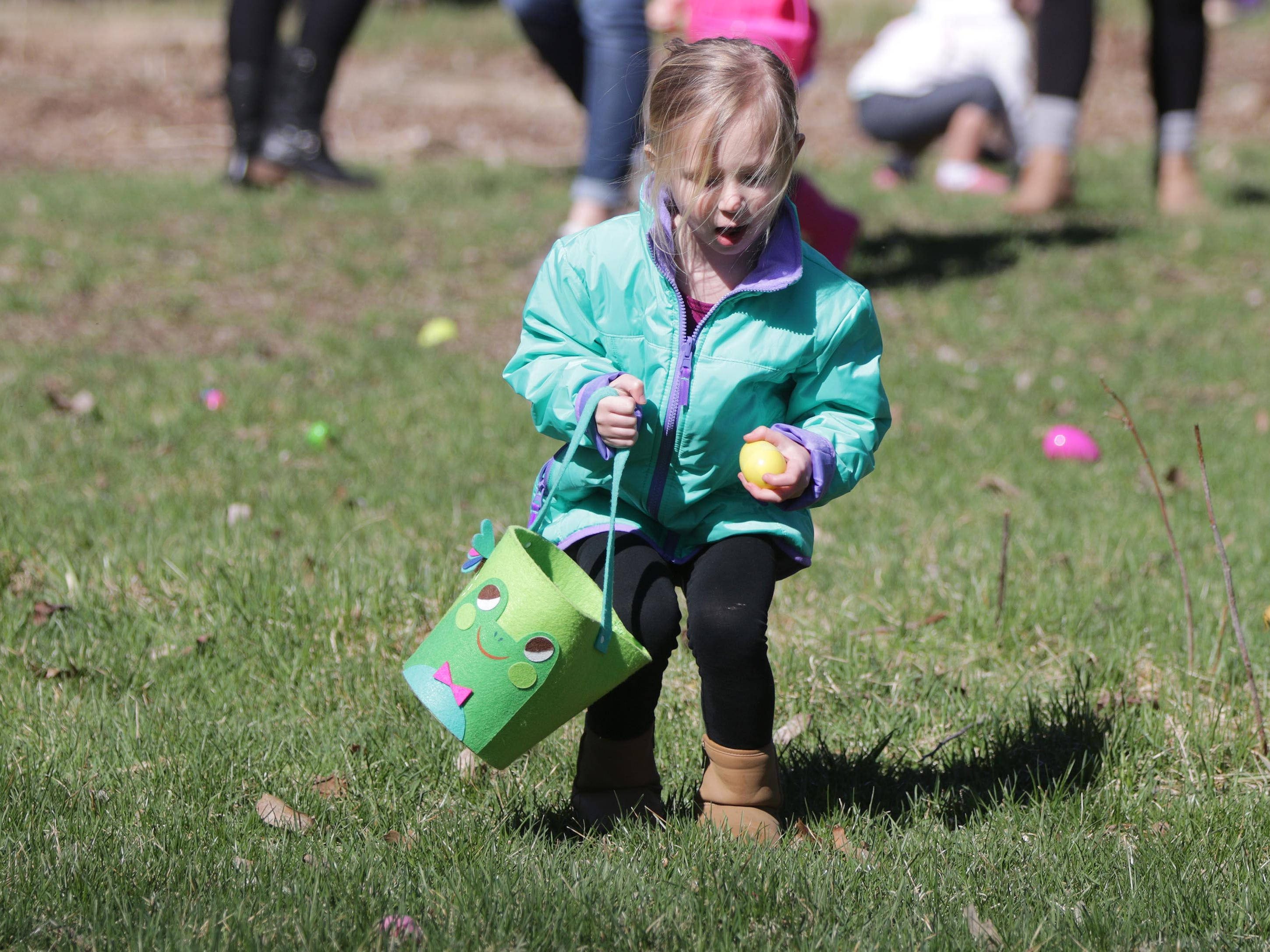 Tessa Jacobchick, 3, of Oostburg, Wis., gathers eggs at the Hocevar Easter Egg Hunt, Saturday, April 20, 2019, in Sheboygan Falls, Wis.  This years marks 25 years for the Hocevar Family holding an Easter egg hunt at their home, according to Kathy Hocevar.