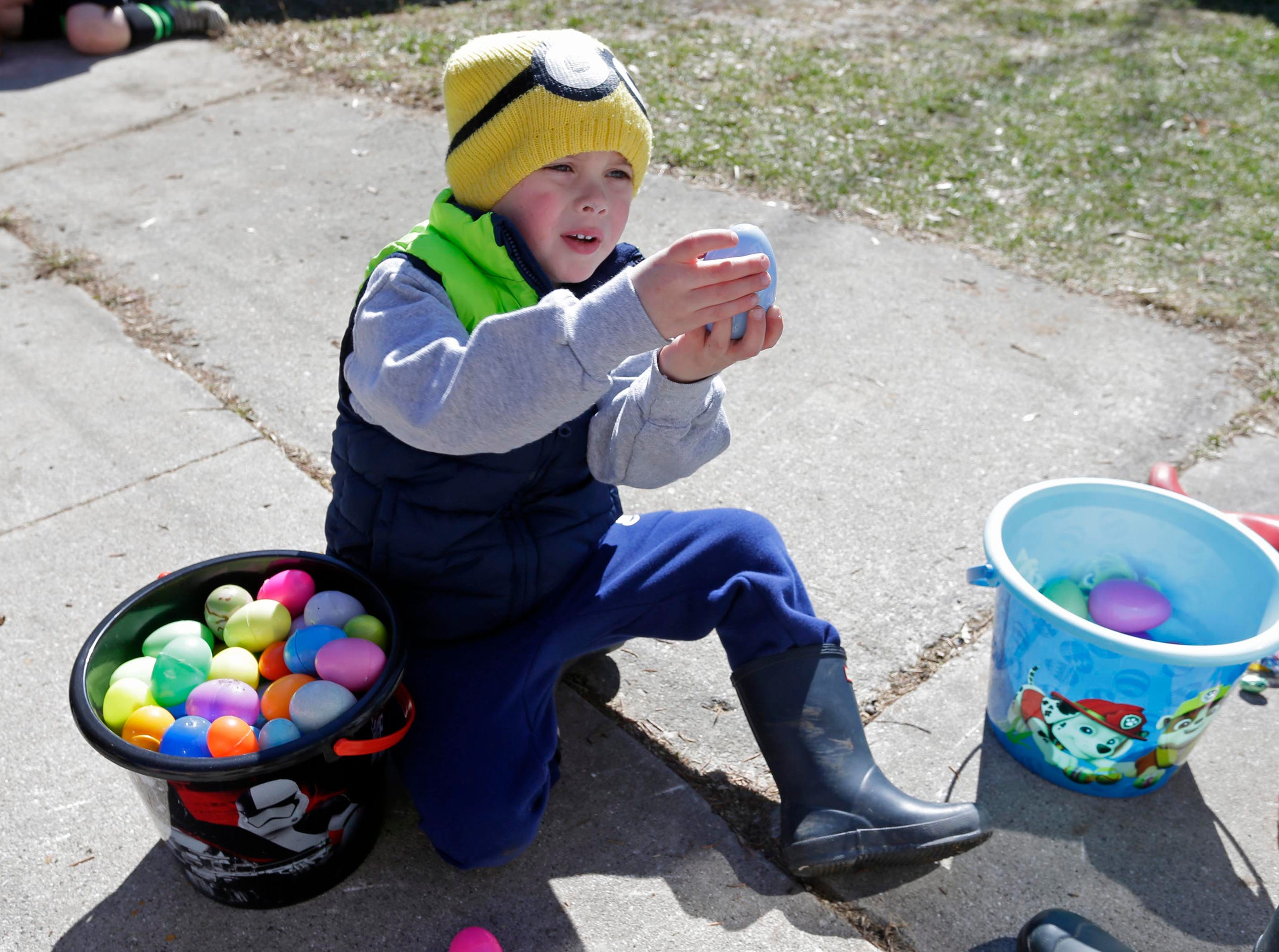 Oliver Ries,6, of Sheboygan, opens his Easter eggs after collecting them at the Hocevar Easter Egg Hunt, Saturday, April 20, 2019, in Sheboygan Falls, Wis.  This years marks 25 years for the Hocevar Family holding an Easter egg hunt at their home, according to Kathy Hocevar.