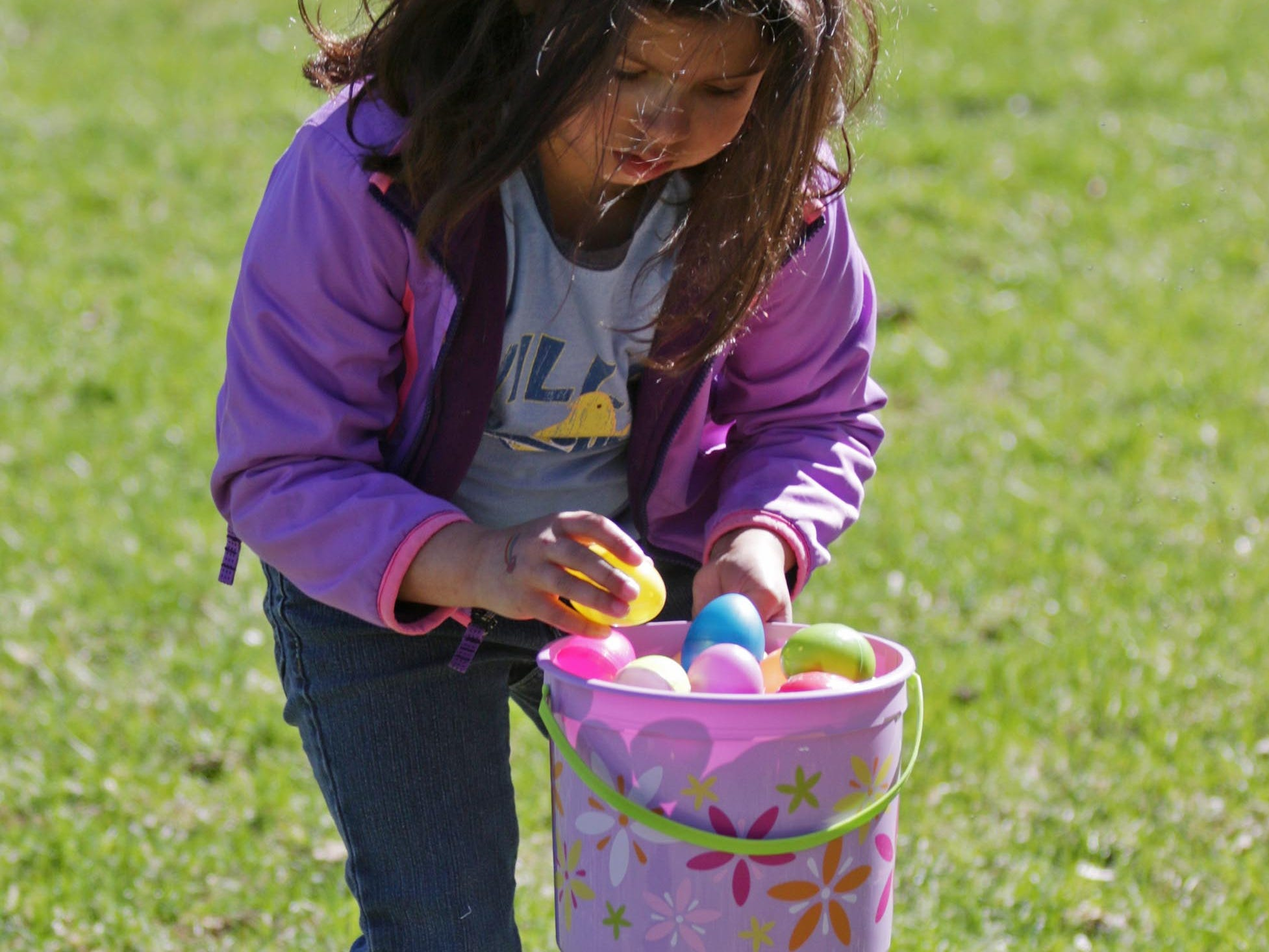 Neenah Rogers, 7, of Sheboygan, gathers eggs at the Hocevar Easter Egg Hunt, Saturday, April 20, 2019, in Sheboygan Falls, Wis.  This years marks 25 years for the Hocevar Family holding an Easter egg hunt at their home, according to Kathy Hocevar.