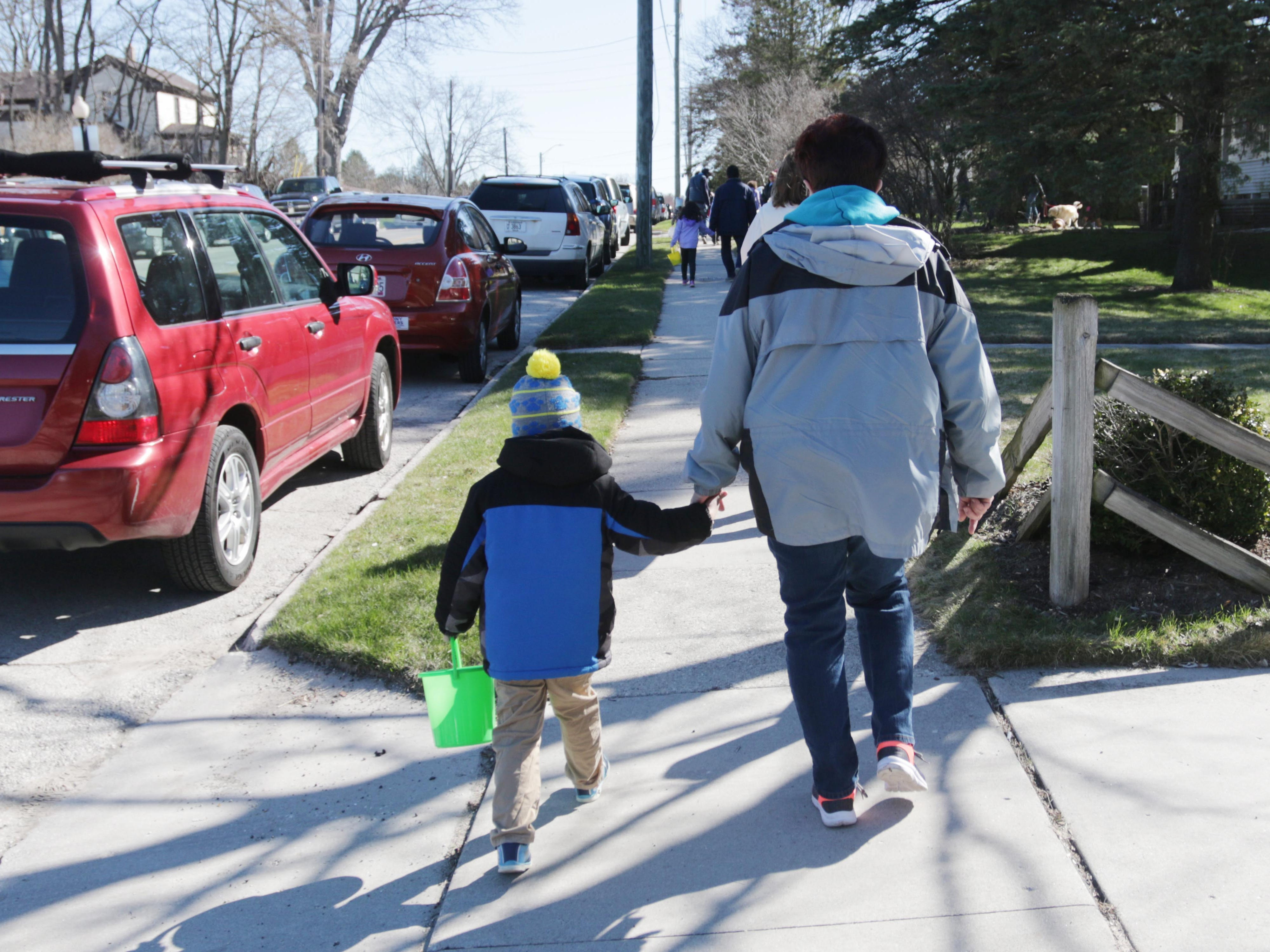 A child and an adult walk to the Hocevar residence to participate in the Hocevar Easter Egg Hunt, Saturday, April 20, 2019, in Sheboygan Falls, Wis.  This years marks 25 years for the Hocevar Family holding an Easter egg hunt at their home, according to Kathy Hocevar.