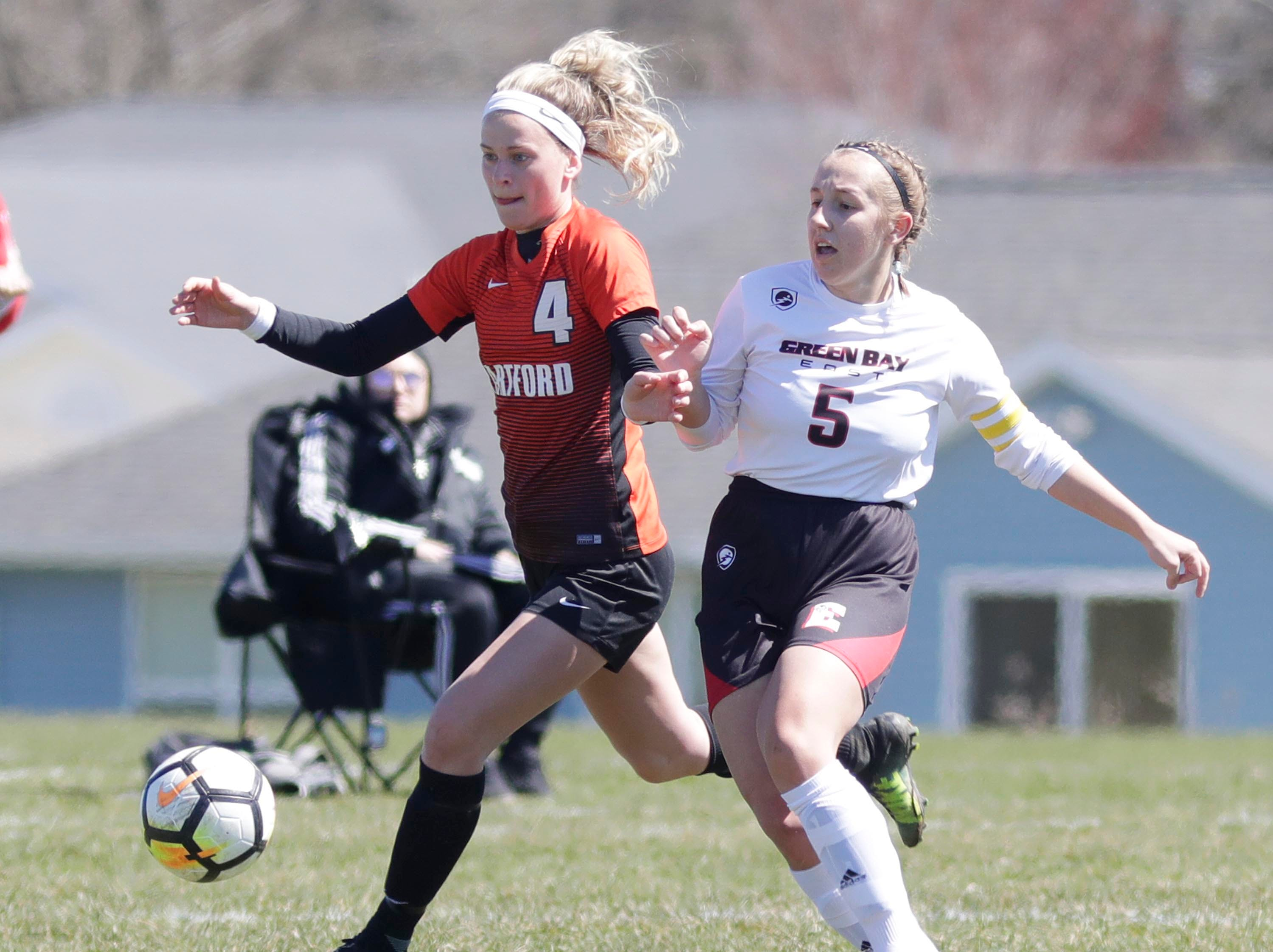 Hardford's Maggie Mueller (4) and Green Bay East's Morgan Baerenwald (5) chase the ball at the Sheboygan South Soccer tournament, Saturday, April 20, 2019, in Sheboygan, Wis.