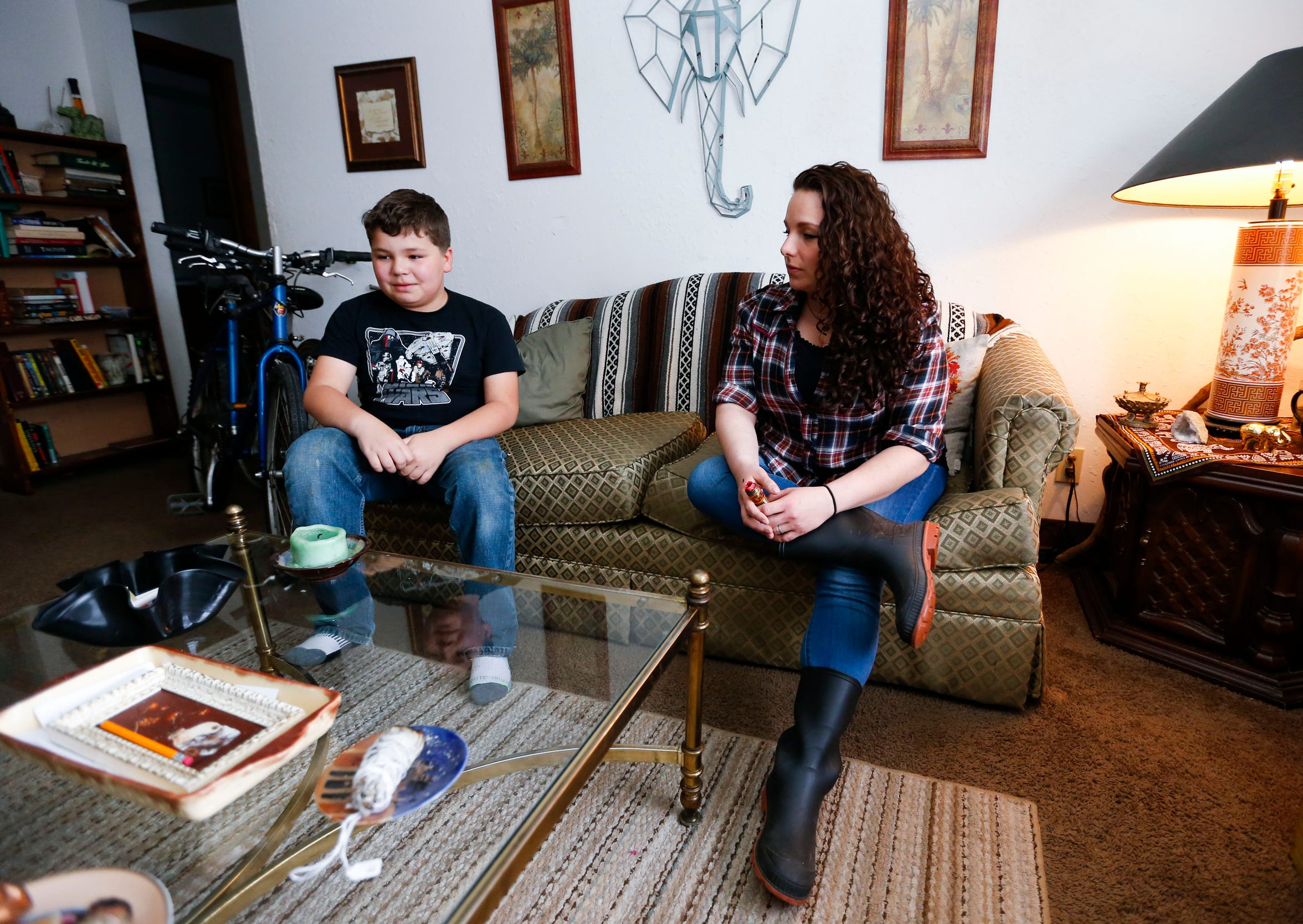 Michelle Gardner sits on the couch in her apartment with her son Sonny, 11, on Thursday, April 4, 2019. Gardner got her first place of her own after being sober and clean for more than two years.