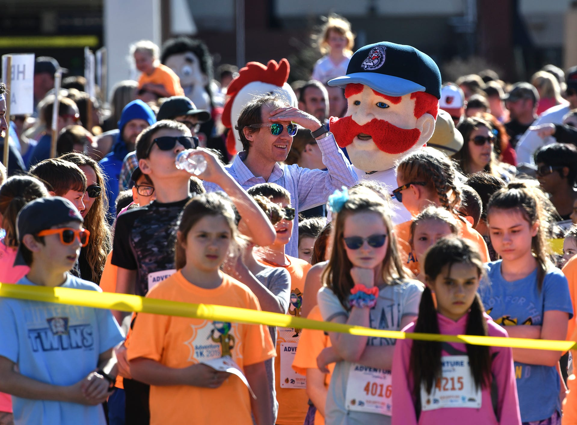Runners gather with local mascots near the starting line of the Kids Adventure 1K Friday in downtown St. Cloud.