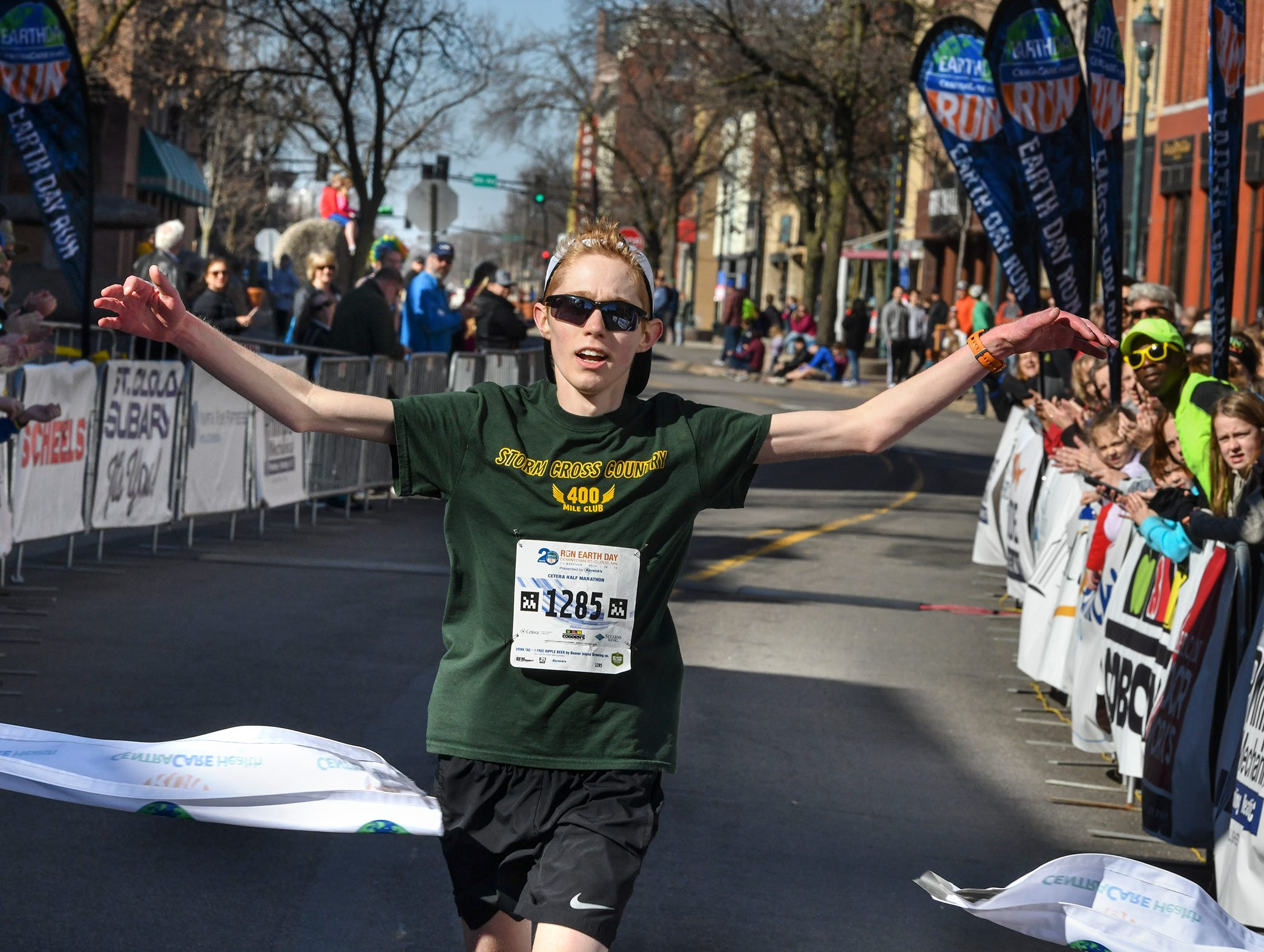 Samuel Ringger raises his arms as he crosses the finish line to win the Cetera Half Marathon as part of CentraCare Health Earth Day Run activities Saturday, April 20, in downtown St. Cloud.