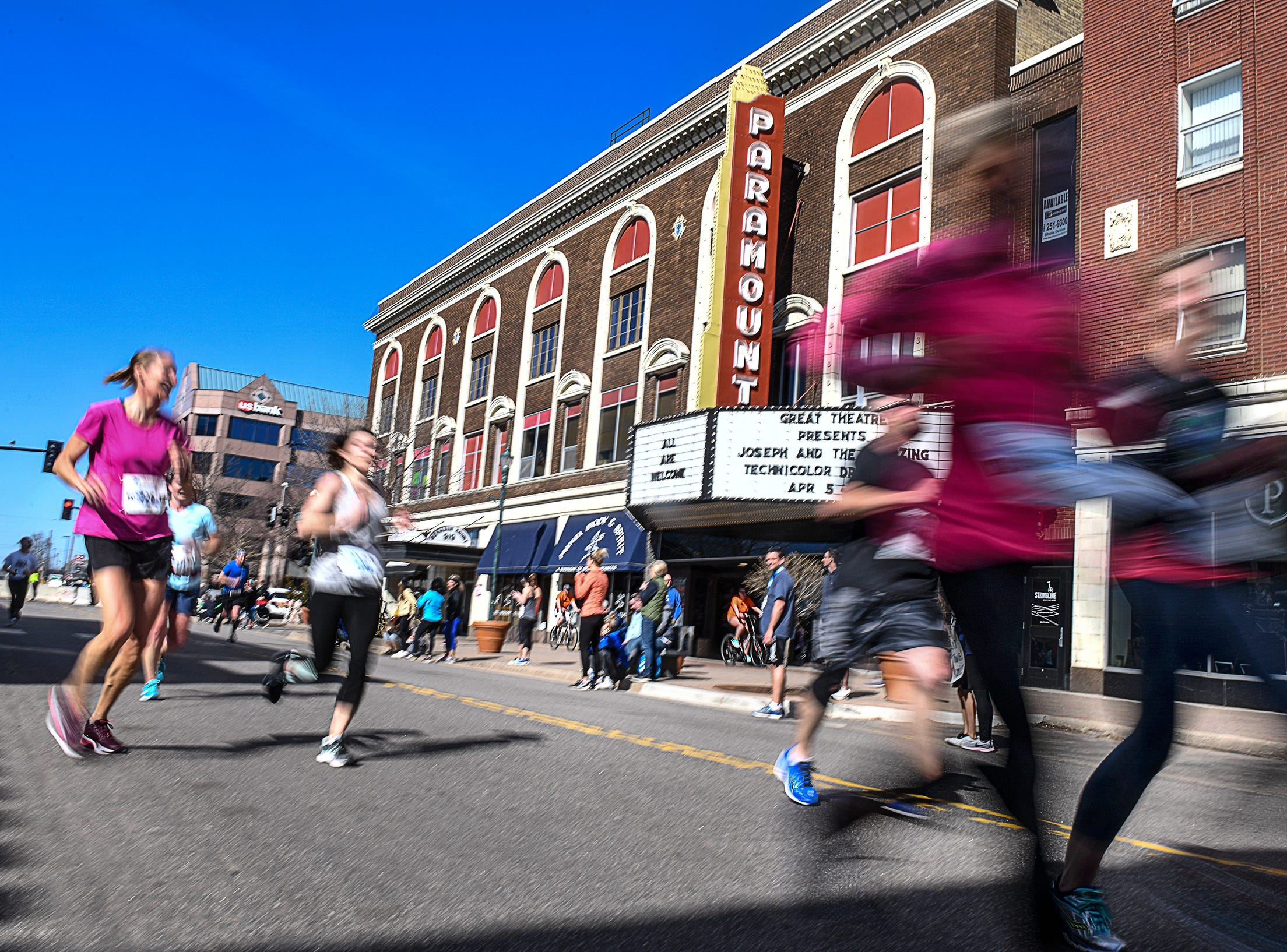 Runners speed past the Paramount Theatre on St. Germain Street during the Cetera Half Marathon as part of CentraCare Health Earth Day Run activities Saturday, April 20, in downtown St. Cloud.