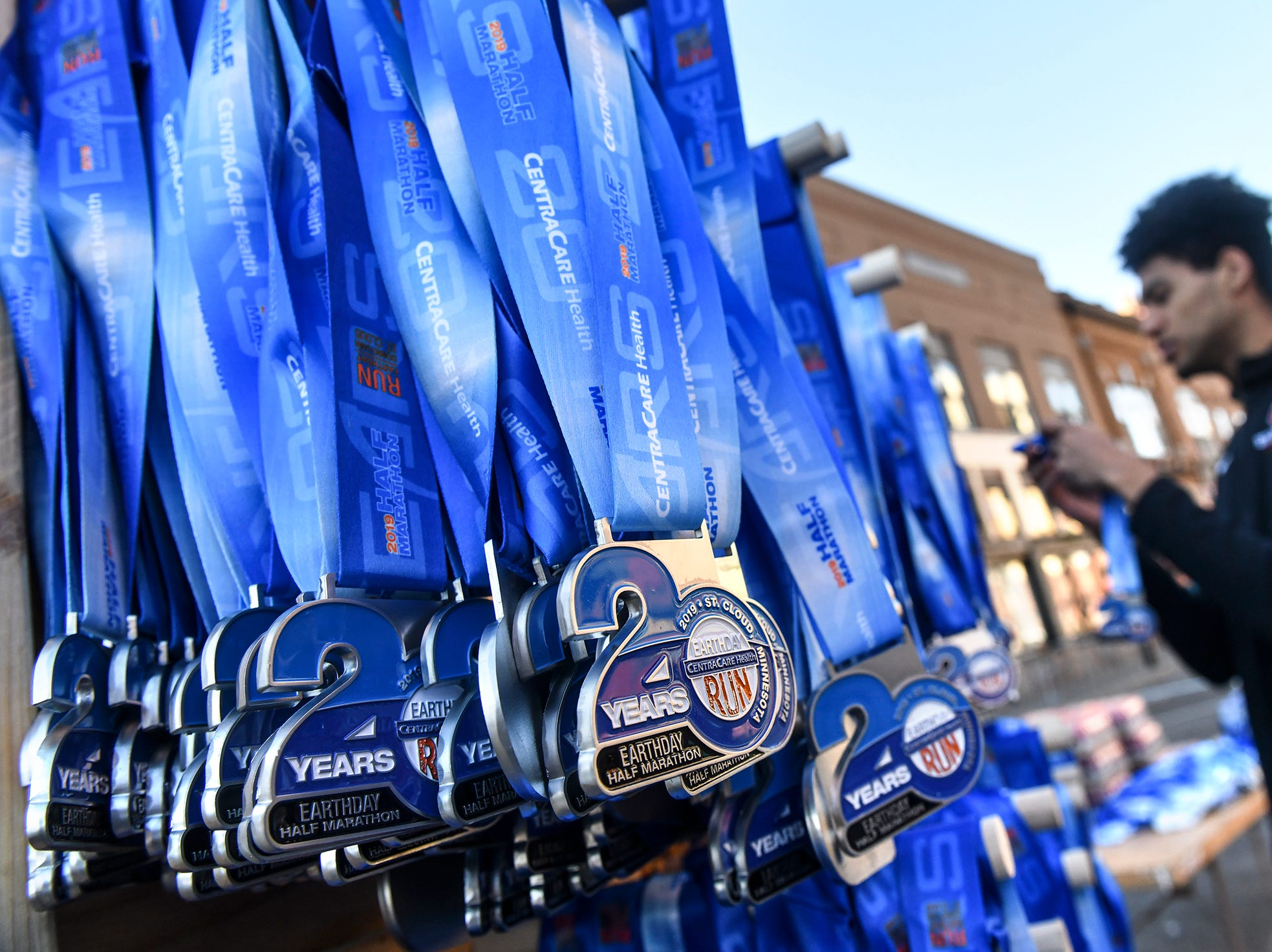 Volunteer Sean Smith arranges medals at the finish line during the Cetera Half Marathon as part of CentraCare Health Earth Day Run activities Saturday, April 20, in downtown St. Cloud.
