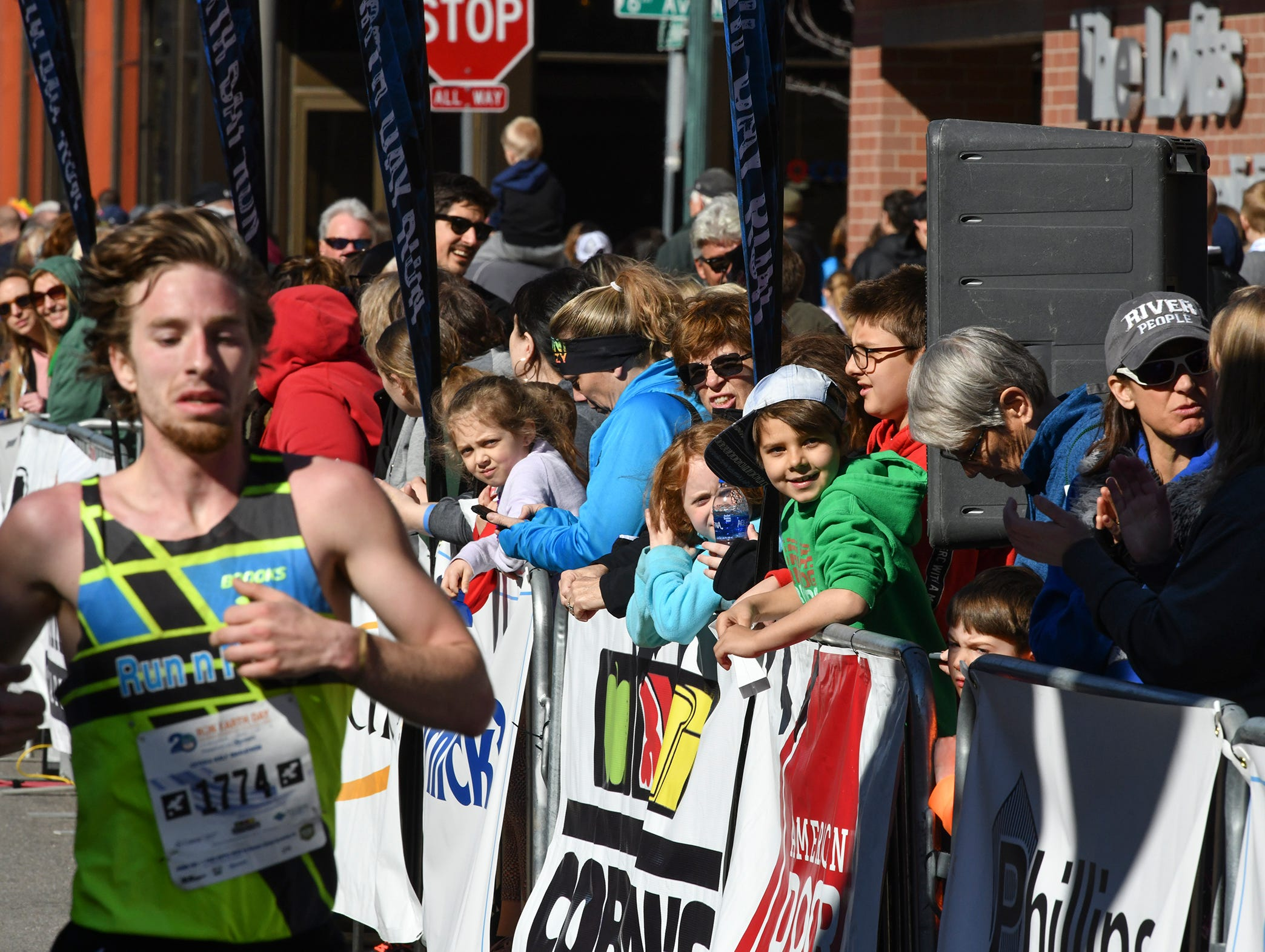 People watch as runners cross the finish line during the Cetera Half Marathon as part of CentraCare Health Earth Day Run activities Saturday, April 20, in downtown St. Cloud.