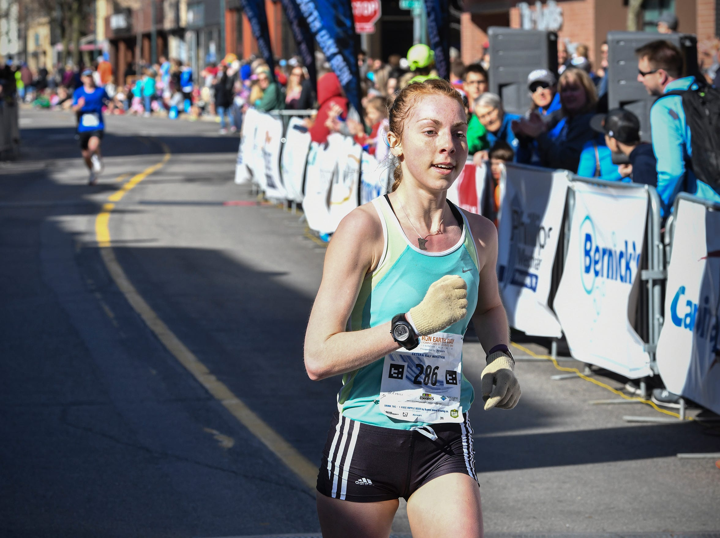 Elena Danielson smiles as she crosses the finish line as the first female finisher during the Cetera Half Marathon as part of CentraCare Health Earth Day Run activities Saturday, April 20, in downtown St. Cloud.
