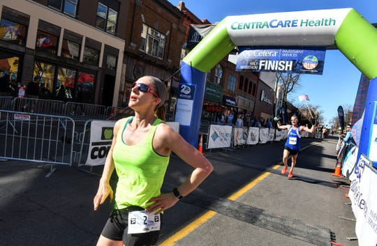Jamie Blumentritt crosses the finish line during the Cetera Half Marathon as part of CentraCare Health Earth Day Run activities Saturday, April 20, in downtown St. Cloud.