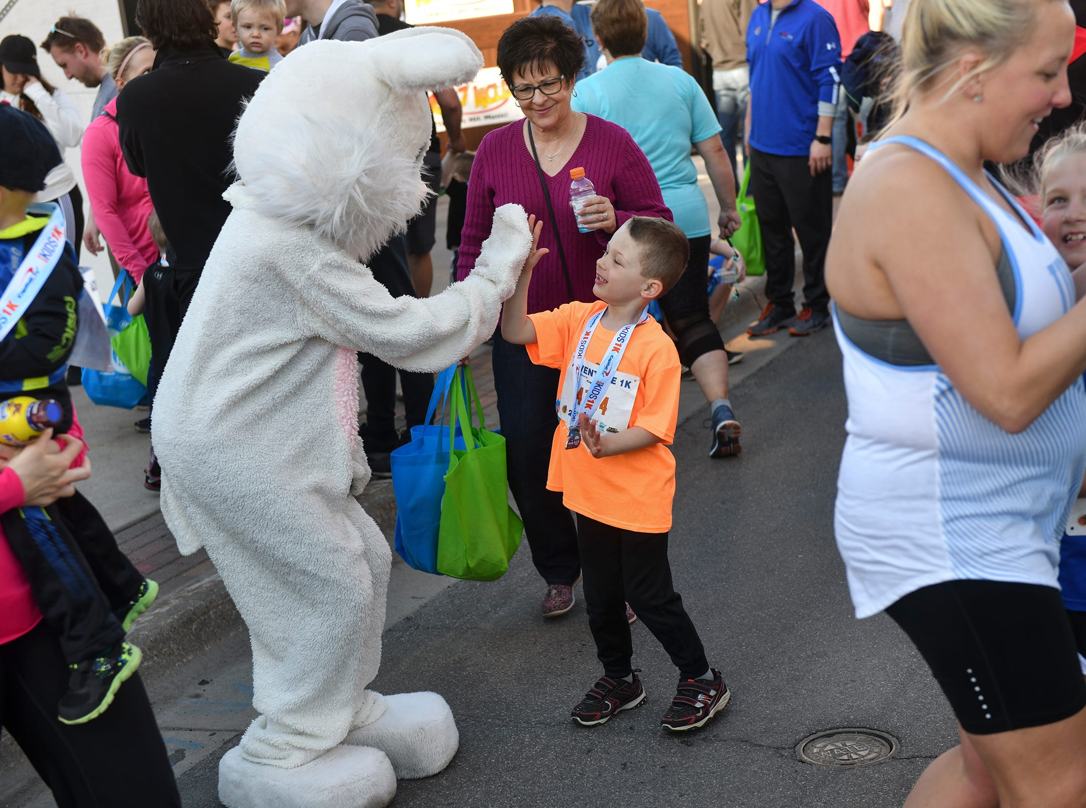 Runners get high-fives from local mascots at the finish line of the Kids Adventure 1K Friday in downtown St. Cloud.