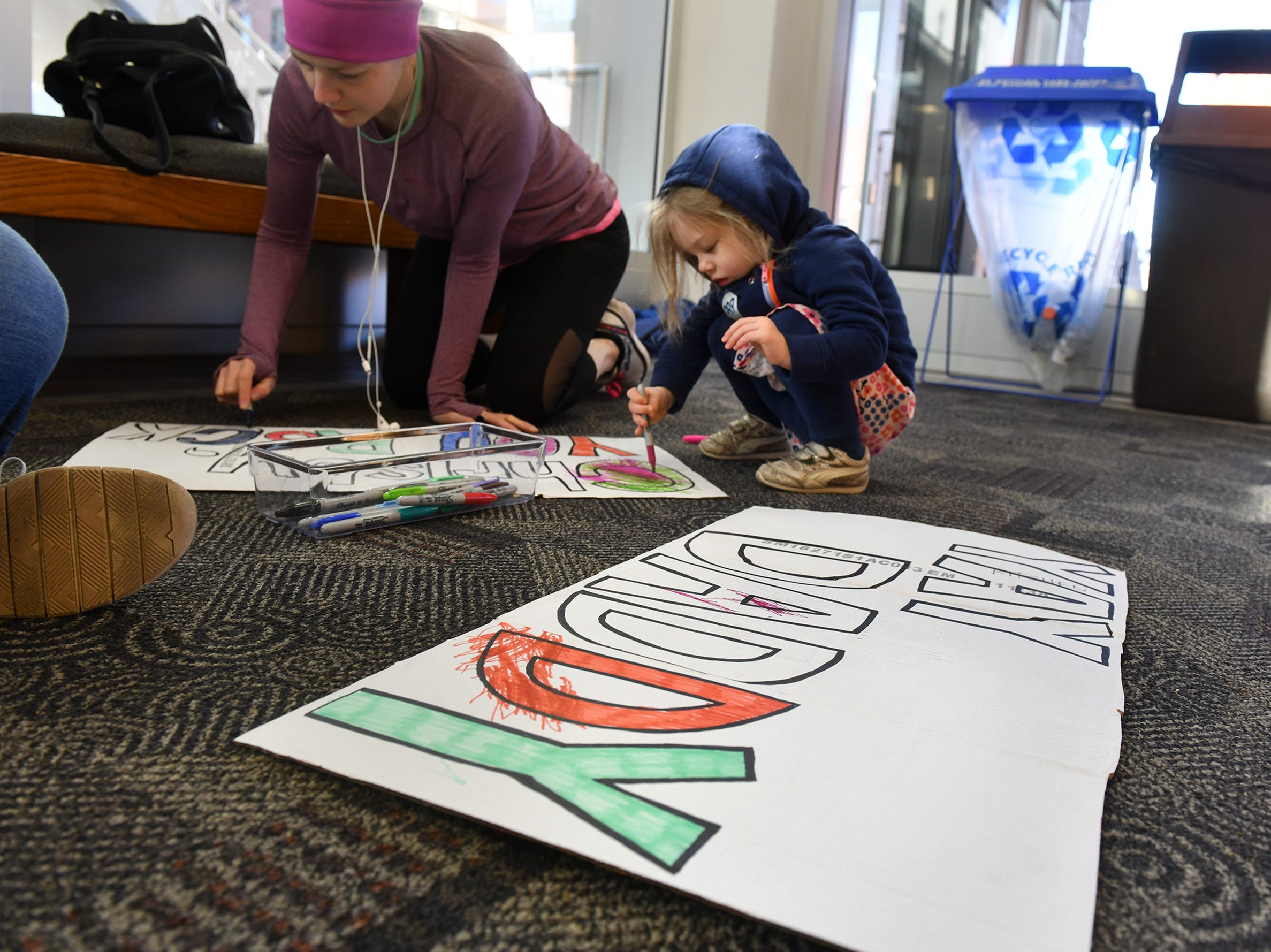 """Margaret Walling takes a break from coloring her """"Yay Daddy"""" sign to help with another sign during the Cetera Half Marathon Saturday, April 20, in downtown St. Cloud."""