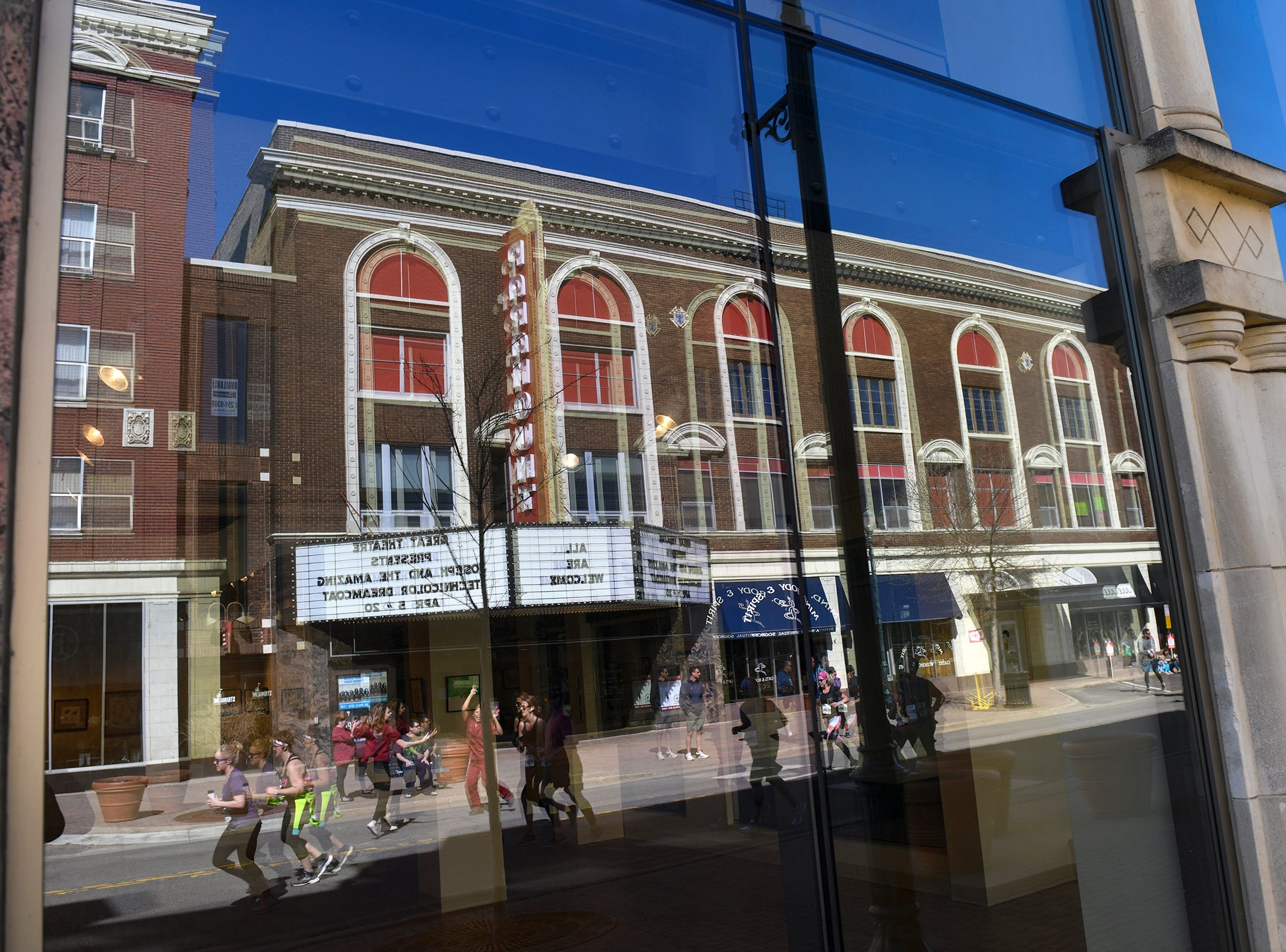 The Paramount Theatre is reflected in windows across the street as runners continue on the race course down St. Germain Street during the Cetera Half Marathon Saturday, April 20, in downtown St. Cloud.