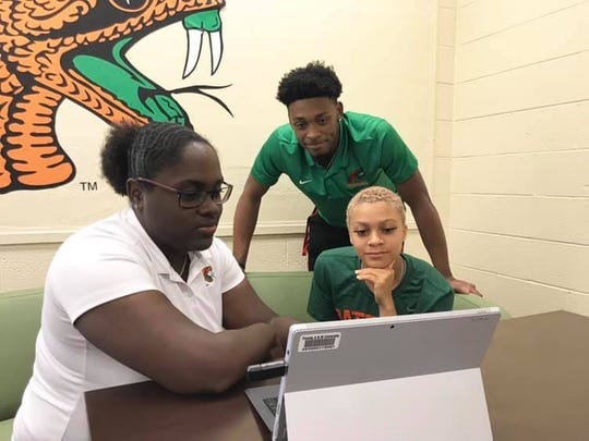 FAMU Athletics learning specialist/Student-Athlete Advisory Committee adviser Ancia Ifill (left) works on finalizing the details for the Fang Awards with men's basketball player Bryce Moragne and women's basketball player Morgan Mitchell.