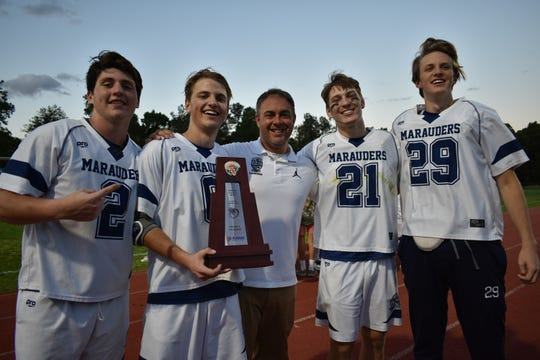Maclay juniors Sam Chase and Matthew Winegardner, head coach Justin VanTassel, and seniors Mark Scott and Jackson Hugill celebrate a lacrosse district title, captured by beating Chiles 11-9 on April 19, 2019.