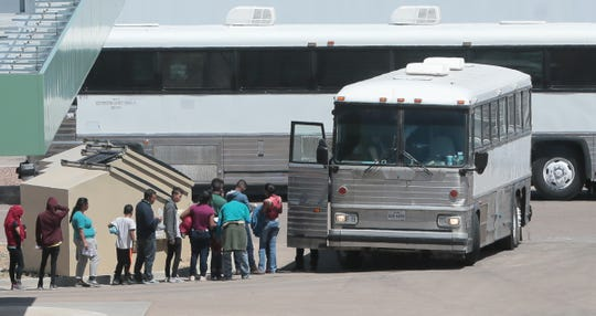 Migrants board a bus Saturday, April 20, 2019, at the Border Patrol station on Hondo Pass Drive in Northeast El Paso. What appears to be a framework for a large structure is laid out nearby.