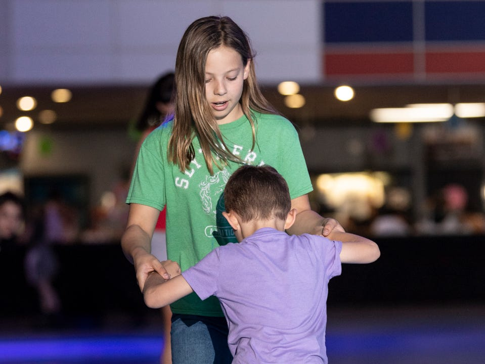 Mackenzie Long, 11, helps a younger skater at RollerTowne in Visalia before the scramble for candy and prizes during their pre-Easter egg hunt on Friday, April 19, 2019.