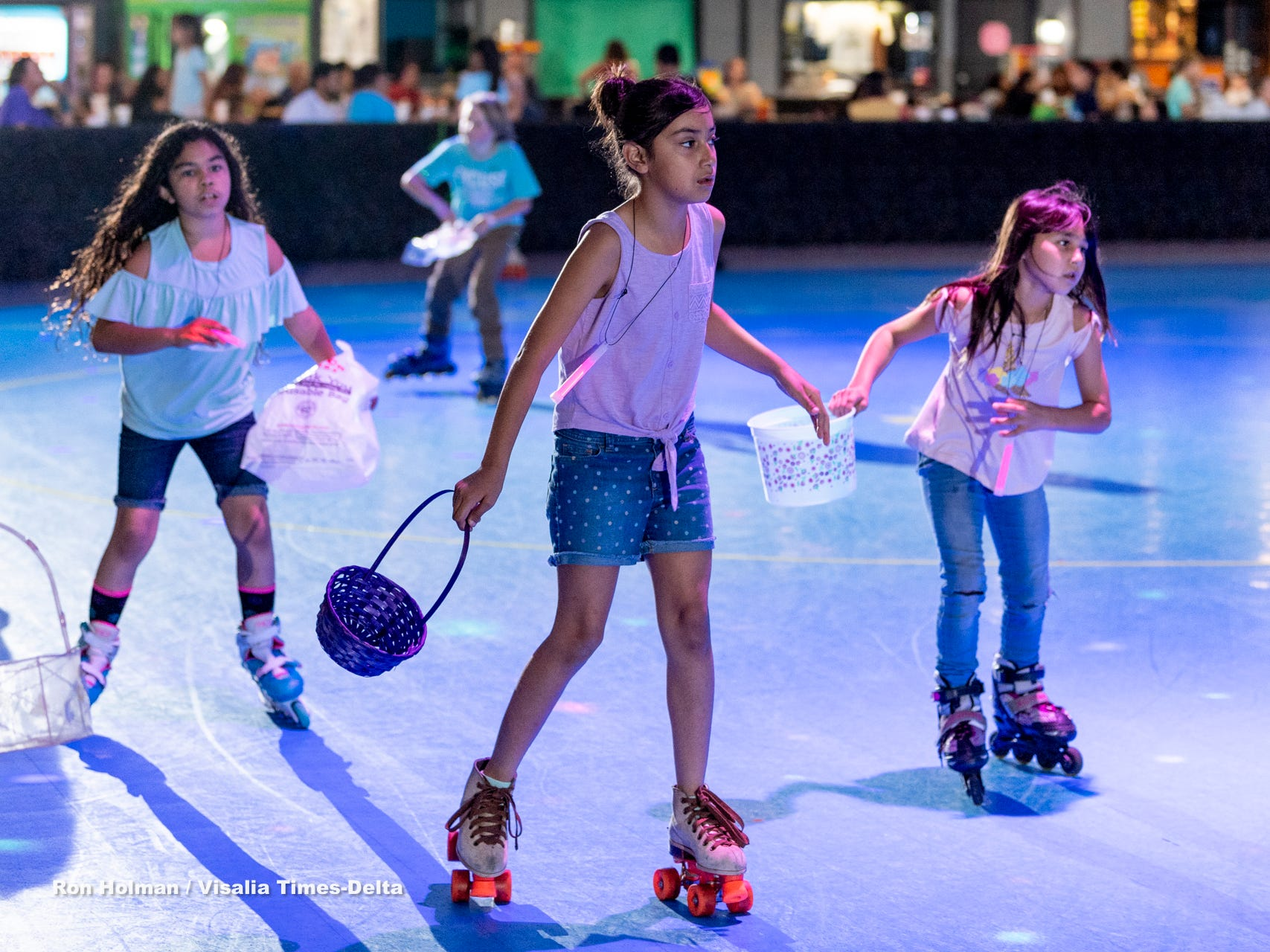 Skaters at RollerTowne in Visalia scramble for candy and prizes during their pre-Easter egg hunt on Friday, April 19, 2019.