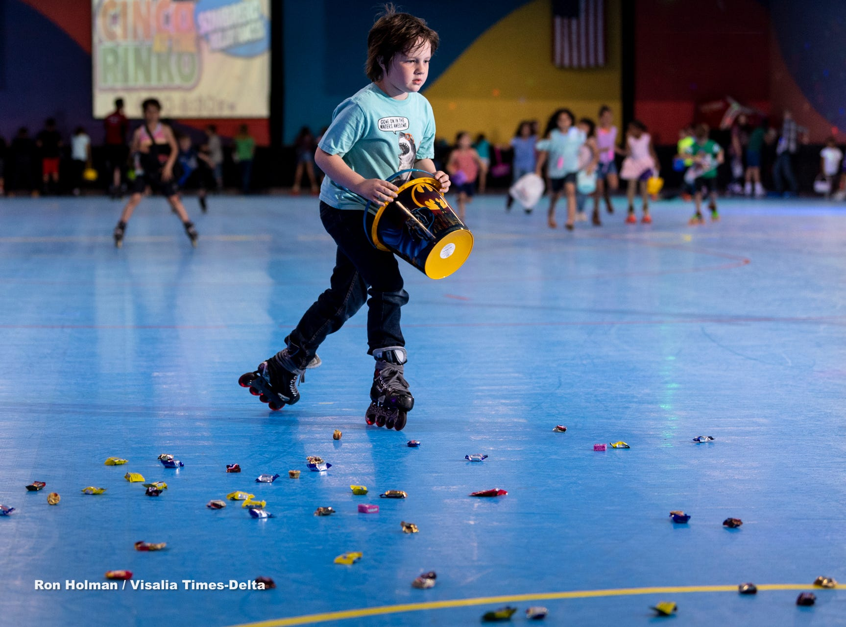 Devan Olson, 7, and other skaters at Roller Towne in Visalia scramble for candy and prizes during their pre-Easter egg hunt on Friday, April 19, 2019.