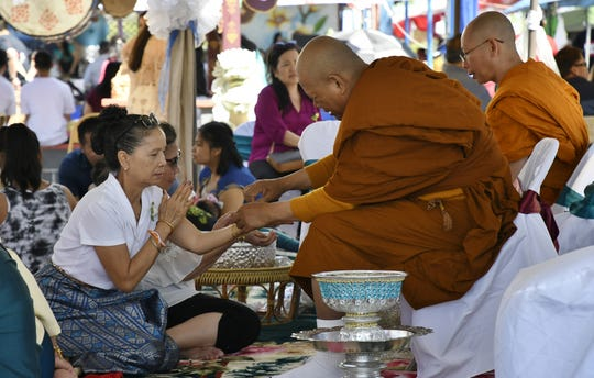 A monk blesses an attendee of the Lao New Year Celebration at the Lao Buddhist Temple of Visalia on Saturday, April 20, 2019.