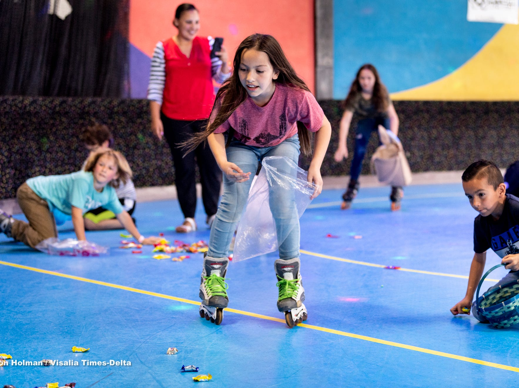 Rachel Schelich, 8, and other skaters at Roller Towne in Visalia scramble for candy and prizes during their pre-Easter egg hunt on Friday, April 19, 2019.