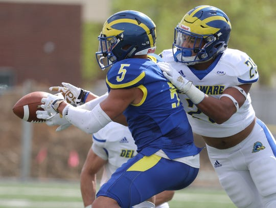 Delaware receiver Gene Coleman II (5) has a reception broken up by linebacker Noah Plack in the Blue vs. White game concluding spring practices at Delaware Stadium Saturday.