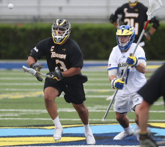 Towson's Alex Woodall (left) moves for the ball on a face-off against Delaware's Thomas Aloe in the Blue Hens' 14-12 loss at Delaware Stadium Saturday.