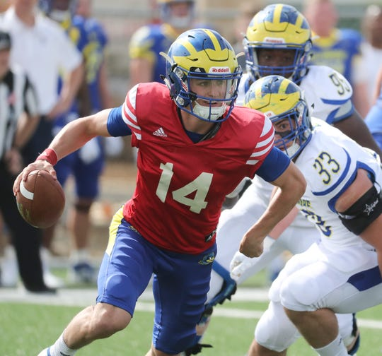 Delaware quarterback Nolan Henderson is flushed from the pocket by linebacker Johnny Buchanan (33) in the Blue vs. White game concluding spring practices at Delaware Stadium Saturday.
