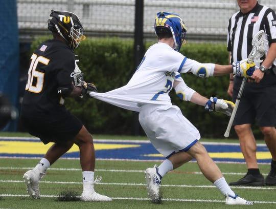 Towson's Jimmie Wilkerson (left) catches the jersey of Delaware's Jackson Finigan in the Blue Hens' 14-12 loss at Delaware Stadium Saturday.