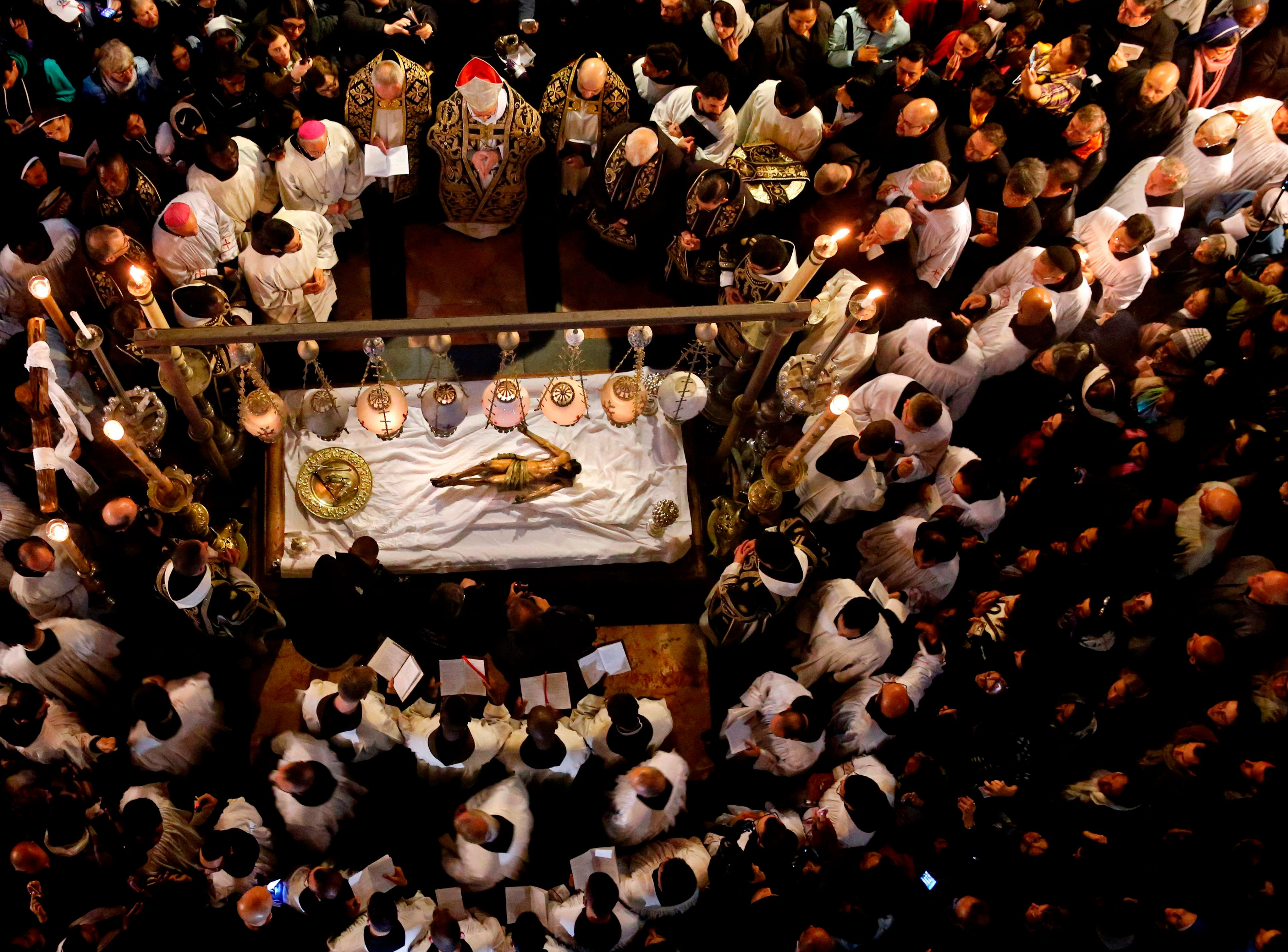 Franciscan friars pray over the statue of Jesus lying down on the Anointing Stone during a reenactment of the Funeral of Jesus inside the Church of the Holy Sepulchre during the Good Friday, in the Old City of Jerusalem, on April 19, 2019. Thousands of Christian pilgrims attend the funeral of Jesus where, according to the tradition, Jesus Christ was crucified, died and resurrected.