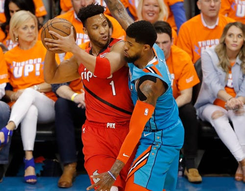 April 19: Trail Blazers guard Evan Turner (1) tries to find room to work against Thunder defender Paul George (13) during Game 3 in Oklahoma City.