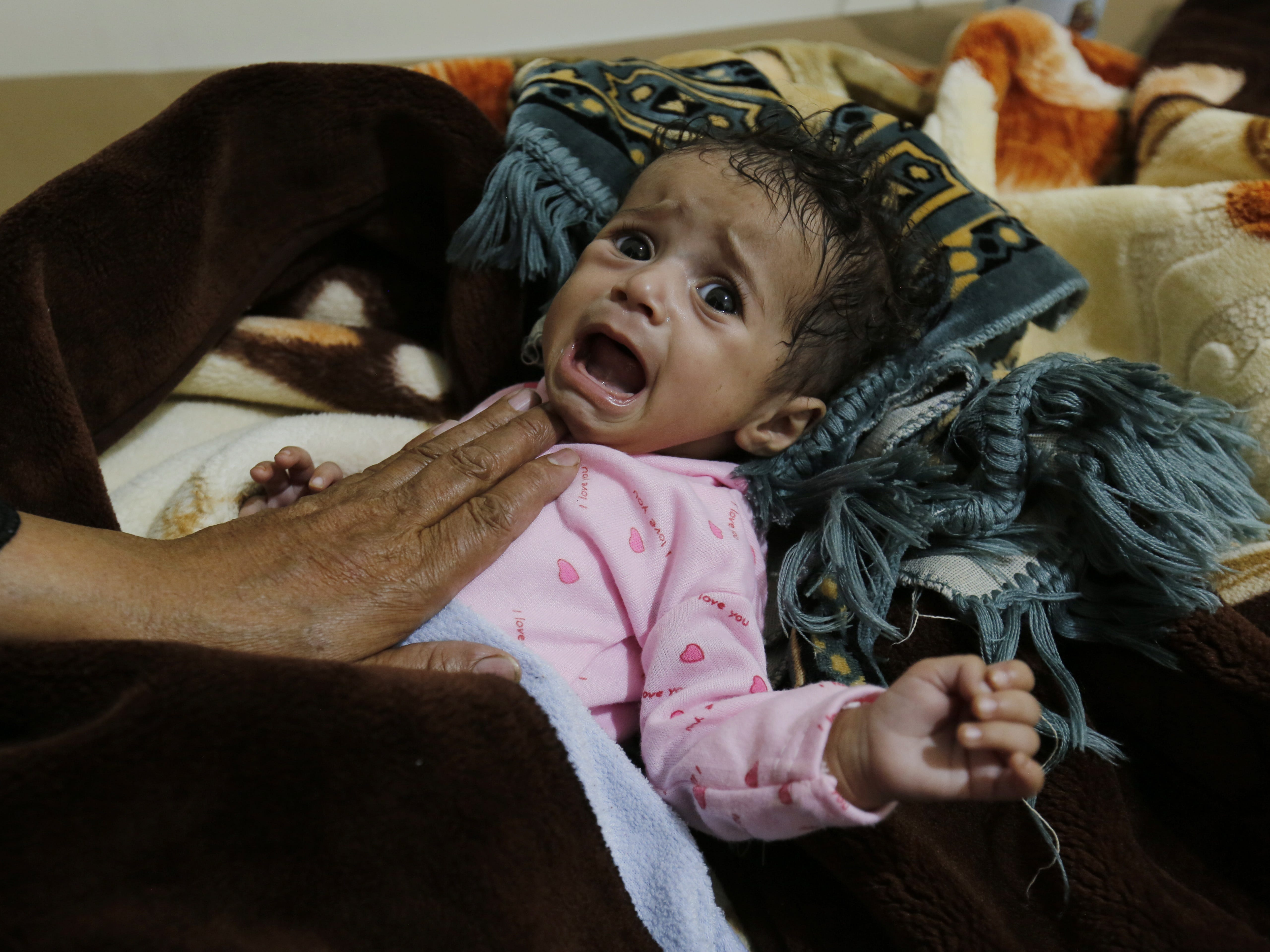 A woman holds her cholera-infected child as he receives treatment at a cholera treatment center amid a cholera outbreak, in Sana'a, Yemen on April 20, 2019. According to reports, nearly 460 deaths of cholera have been registered in Yemen since the beginning of 2019 while more than 223 thousand suspected cases have been reported so far. Nearly a quarter of the cases of children are under five.
