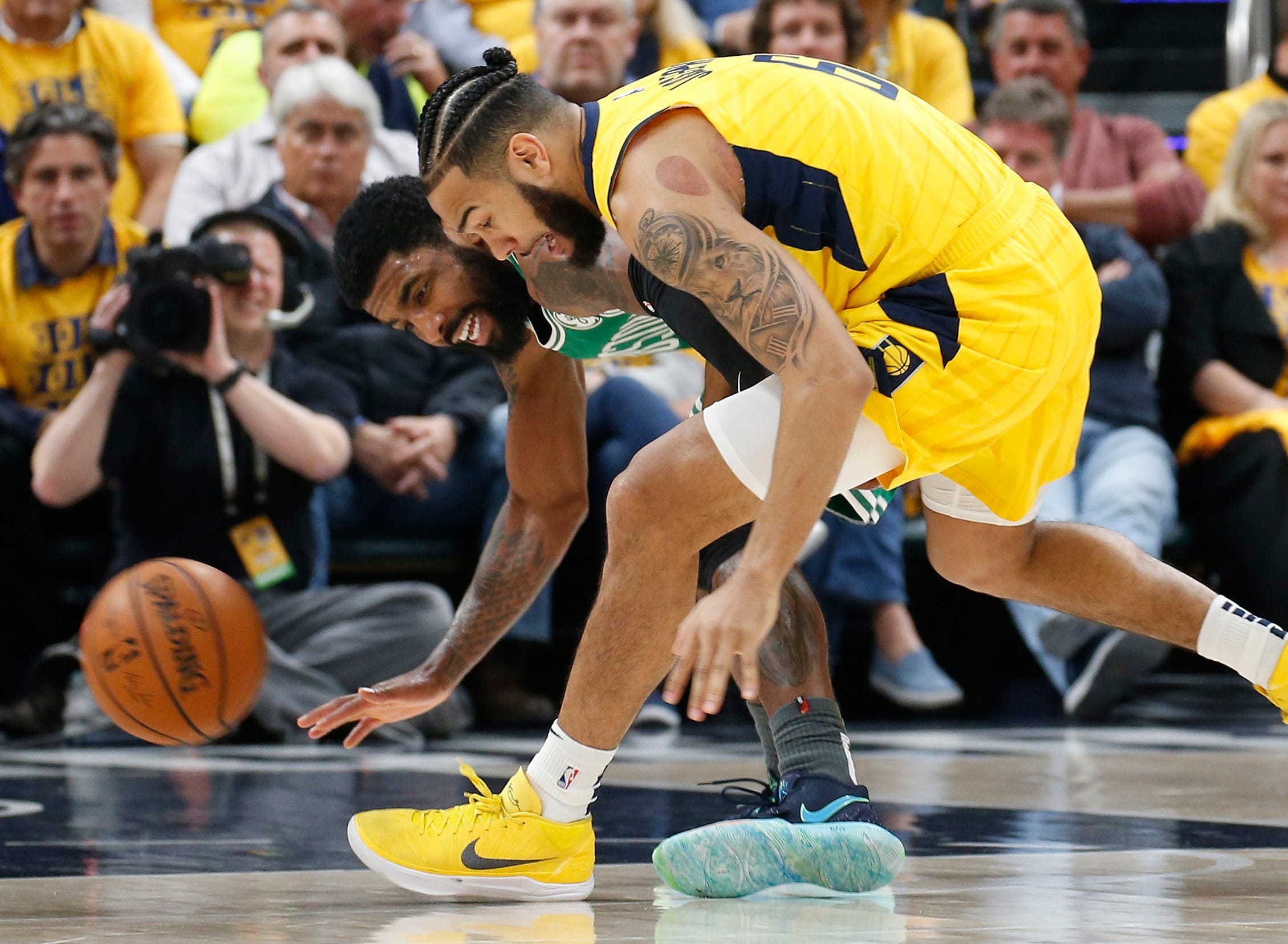 April 19: Celtics guard Kyrie Irving (11) and Pacers guard Cory Joseph (6) chase after a loose ball during Game 3 in Indianapolis.