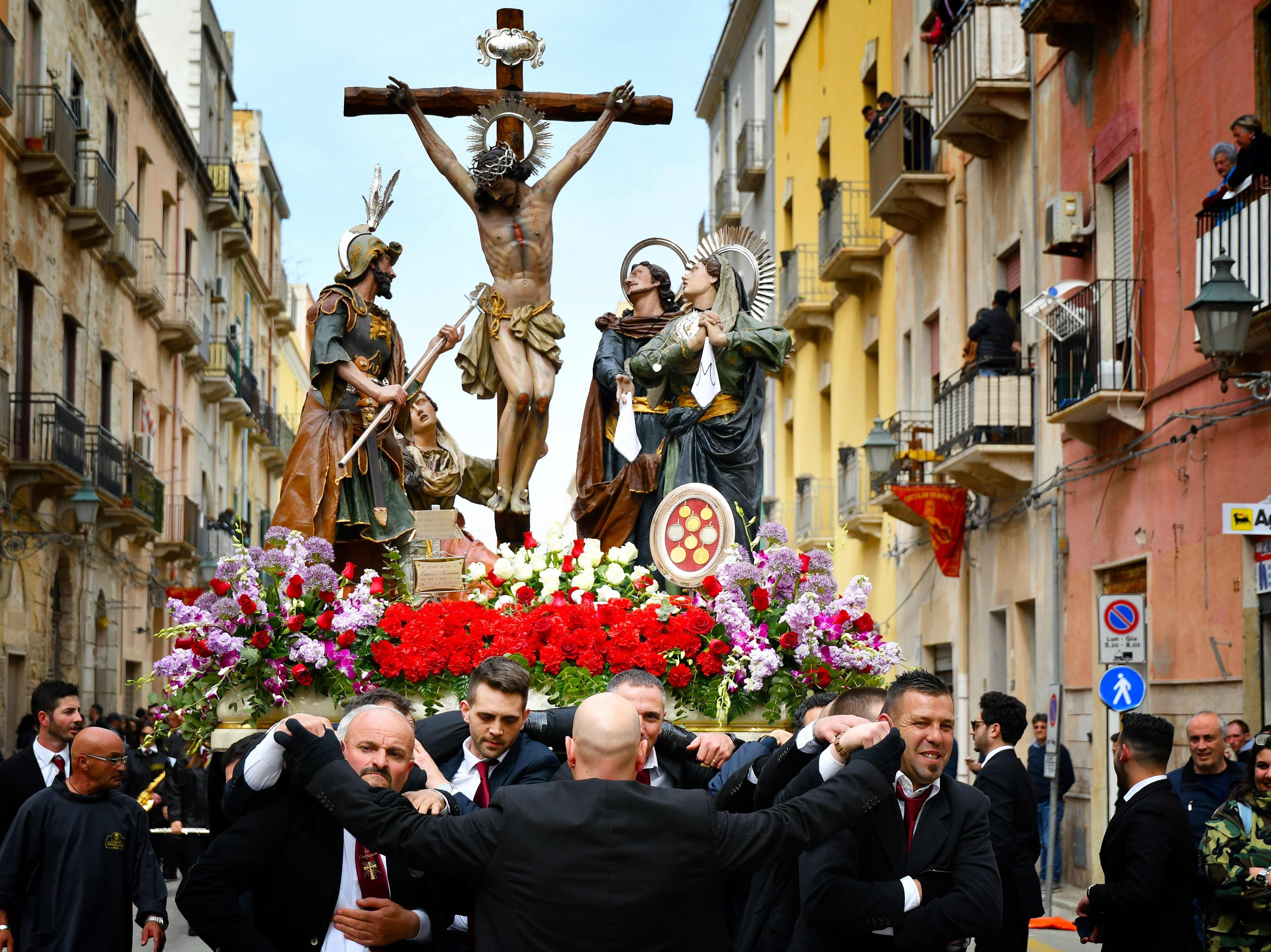Men carry a Christ Crucified and statues of the Passion of the Christ during the traditional Easter Procession of the Mysteries (Processione Dei Misteri) in Trapani, Sicily, on April 20, 2019.