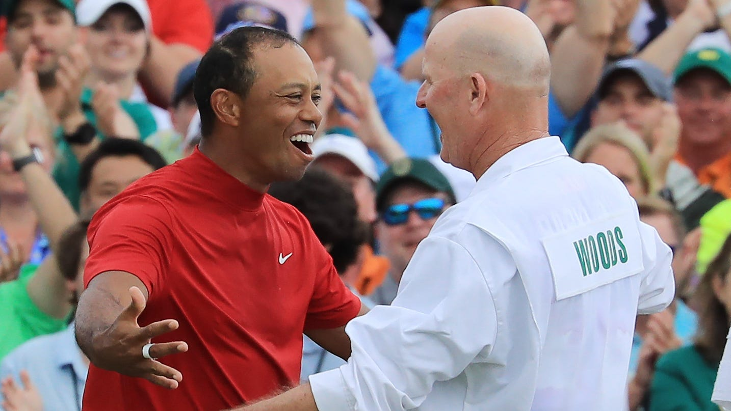 Tiger Woods celebrates with caddie Joe LaCava on the 18th green after winning the Masters.