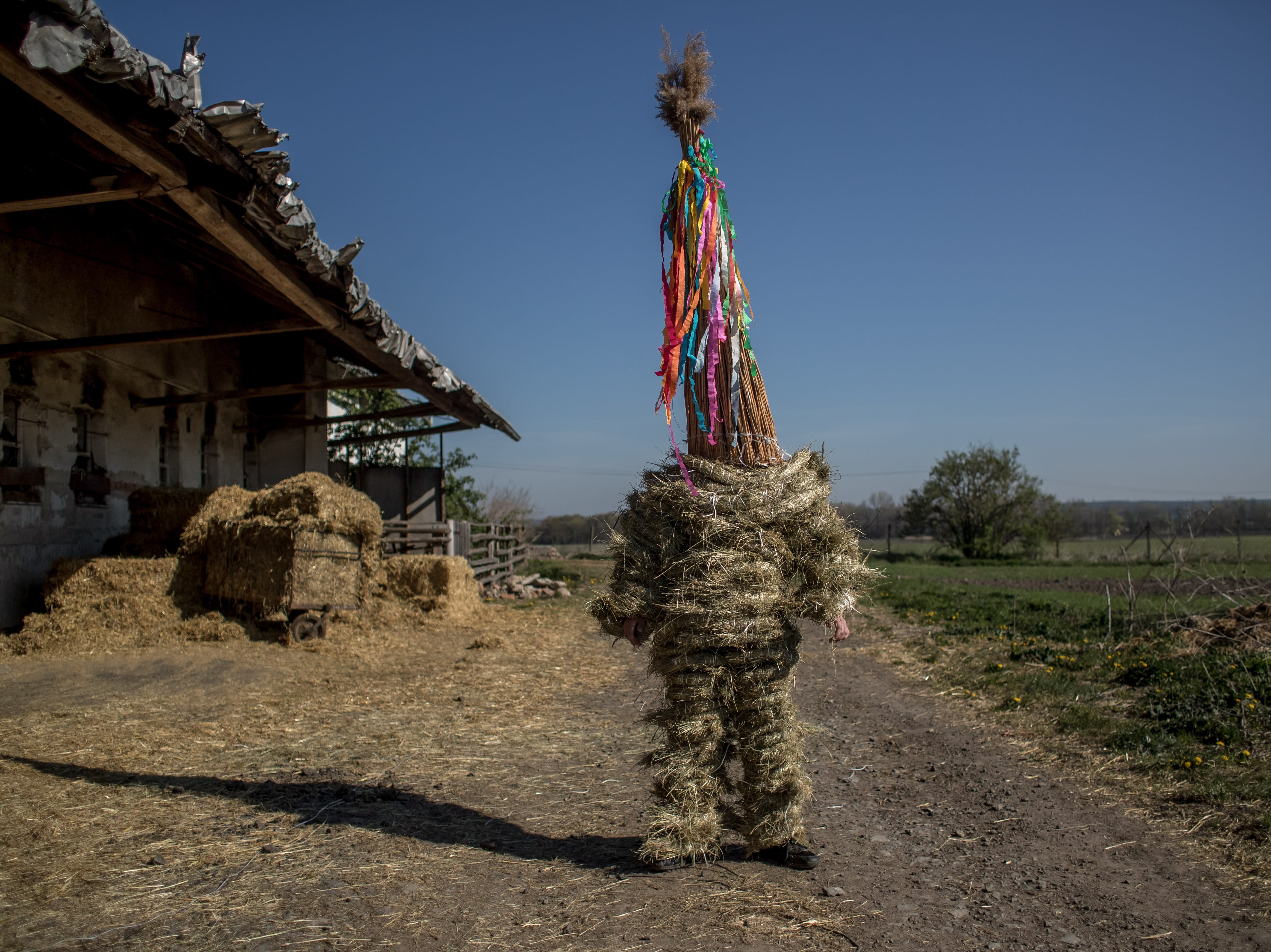 A boy dressed in a hay suit prepares for an Easter procession called 'Marching Judas' in the village of Stradoun, Czech Republic on April 20, 2019. The 'Marching Judas' is an old Czech Easter tradition of dressing up the oldest teenage boy in a village in a hay suit and a high cap from reed symbolizing Judas, who betrayed Jesus Christ. The boy in a hay suit, along with other teenagers walk through the village house by house pushing wooden rattles and recite carol about Judas betray. Marching Judas tradition occurs in few villages in Pardubice region and was registered on the UNESCO List of the Intangible Cultural Heritage of Humanity in 2012.