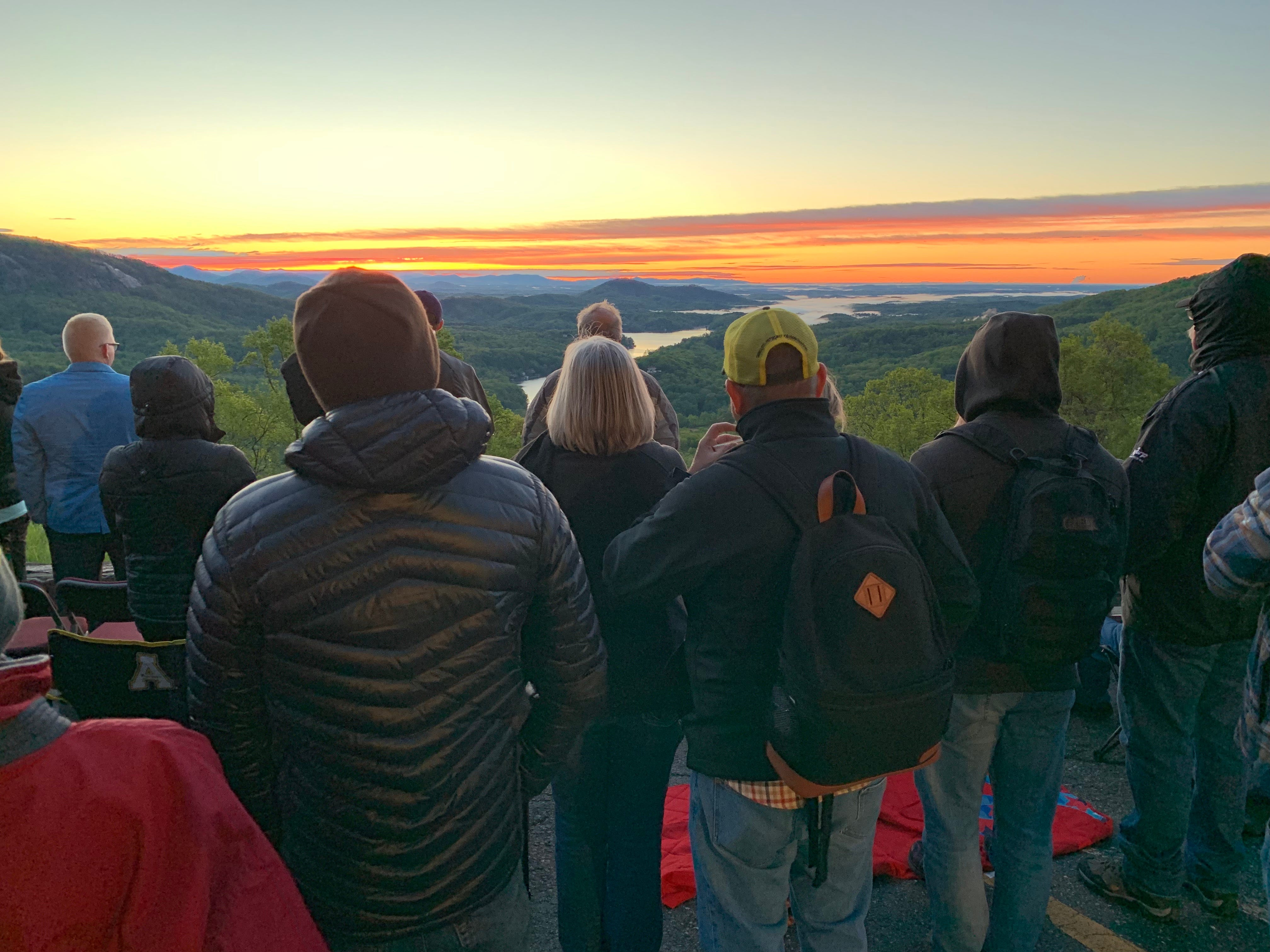 Worshipers watch the sunrise over Lake Lure from Chimney Rock Park's Easter sunrise service on April 21, 2019.
