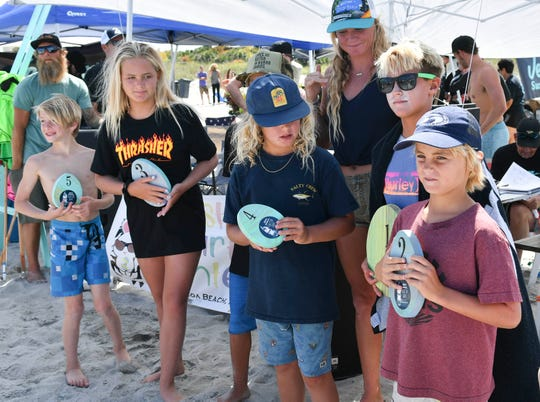 "Winning menehunes hold up their trophies during the Easter Surf Fest. They competed in a ""free-for-all."""