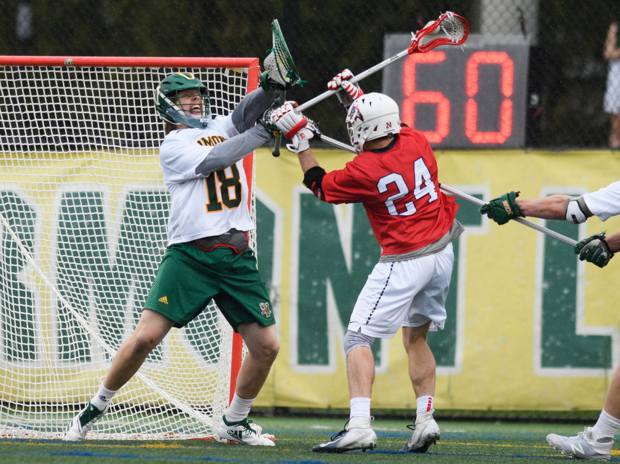 Vermont goalie Nick Washuta (18) tries to save a shot by Stony Brook's Tom Dugan (24) during the men's lacrosse game between the Stony Brook Sea Wolves and the Vermont Catamounts at Virtue Field on Saturday afternoon April 20, 2019 in Burlington, Vermont.